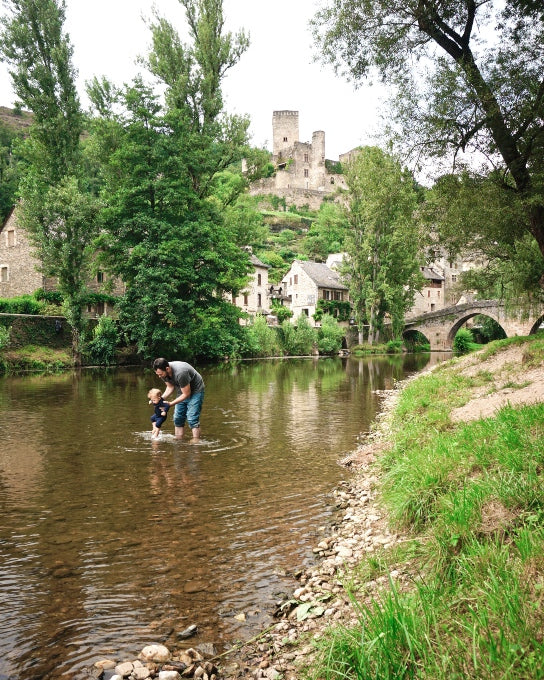 Whitney's husband Adam rinses West's feet in the Aveyron river in the medieval village of Belcastel (Aveyron, France), Whitney's home-away-from-home for the last ten years.