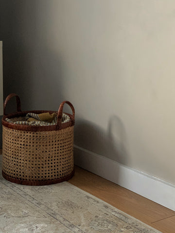 Rattan basket and beige rug against a warm neutral painted wall