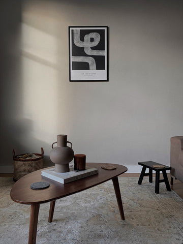 Minimally Styled living room with mid century furniture and the evening light on the warm beige painted wall