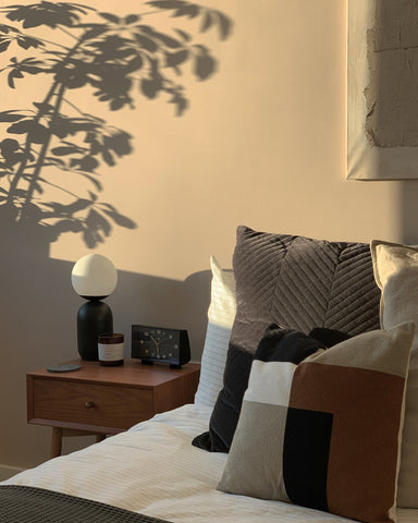 Morning sun casts a shadow on warm neutral wall with soft bedding in the foreground