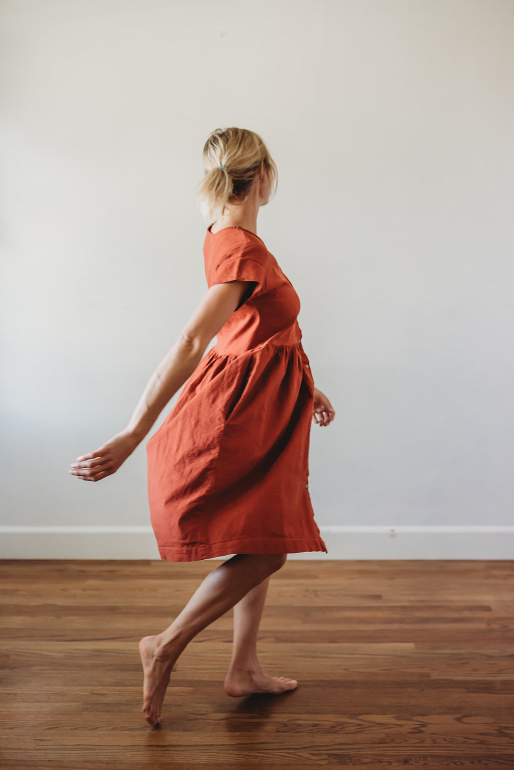 woman twirling wearing a rust orange linen short sleeved dress