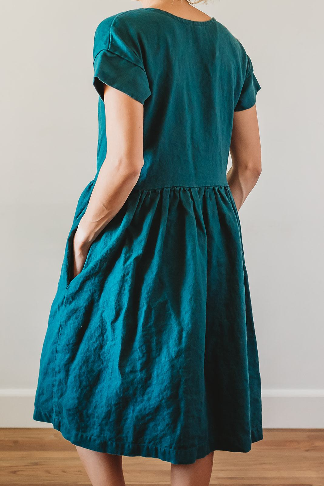 a blue green linen dress with gathered skirt and pockets worn by a model as shown from the back
