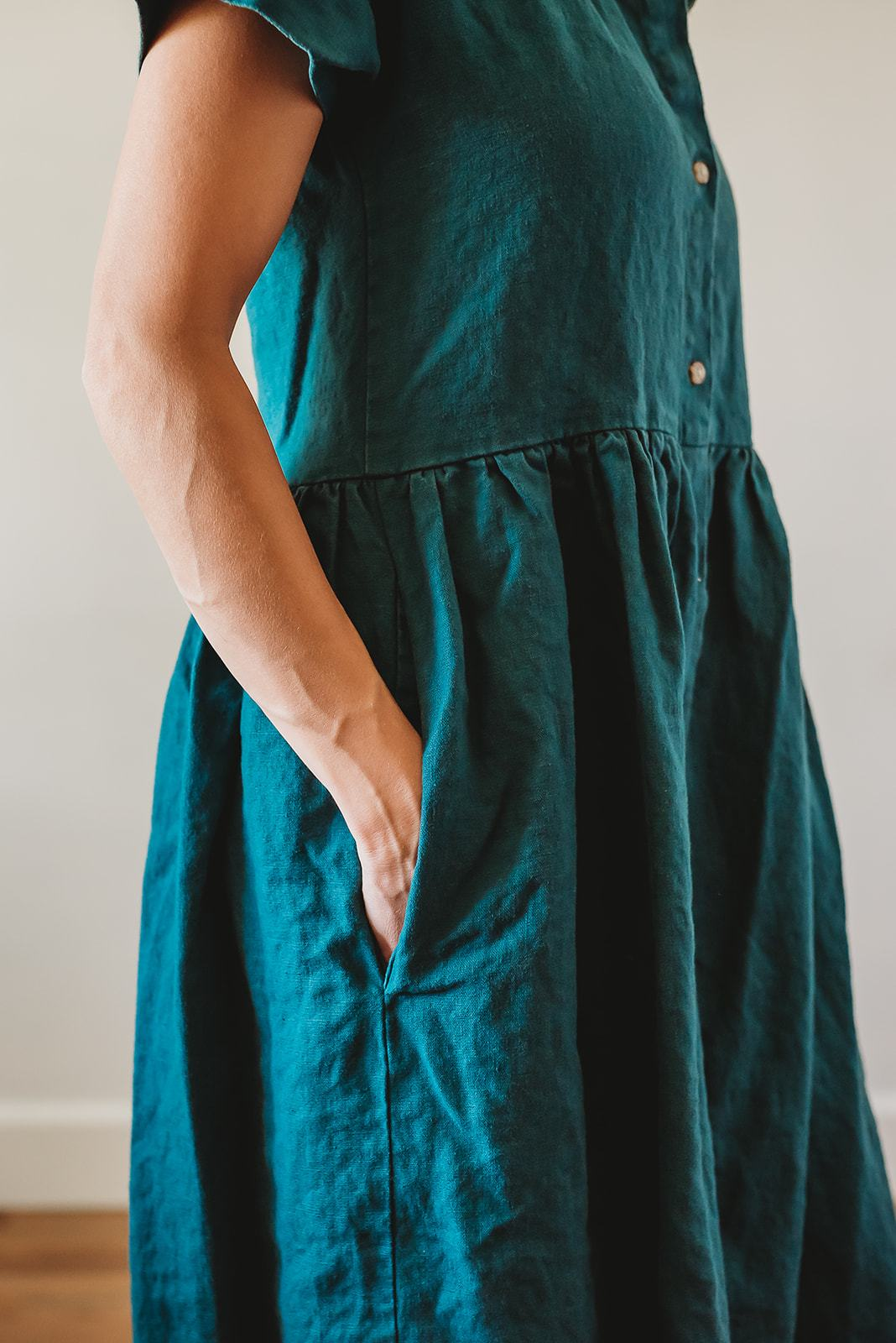 a modelled teal linen dress shown from the side view, hand in pocket