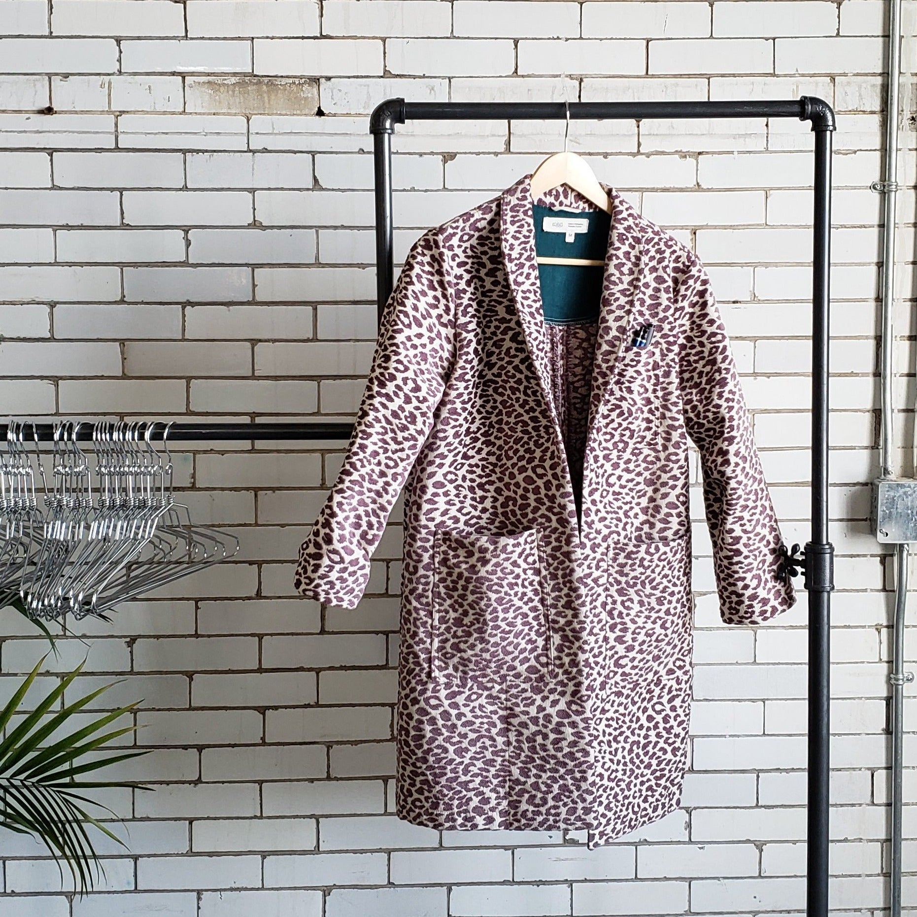 cheetah print spring lab coat hanging on a clothing rack