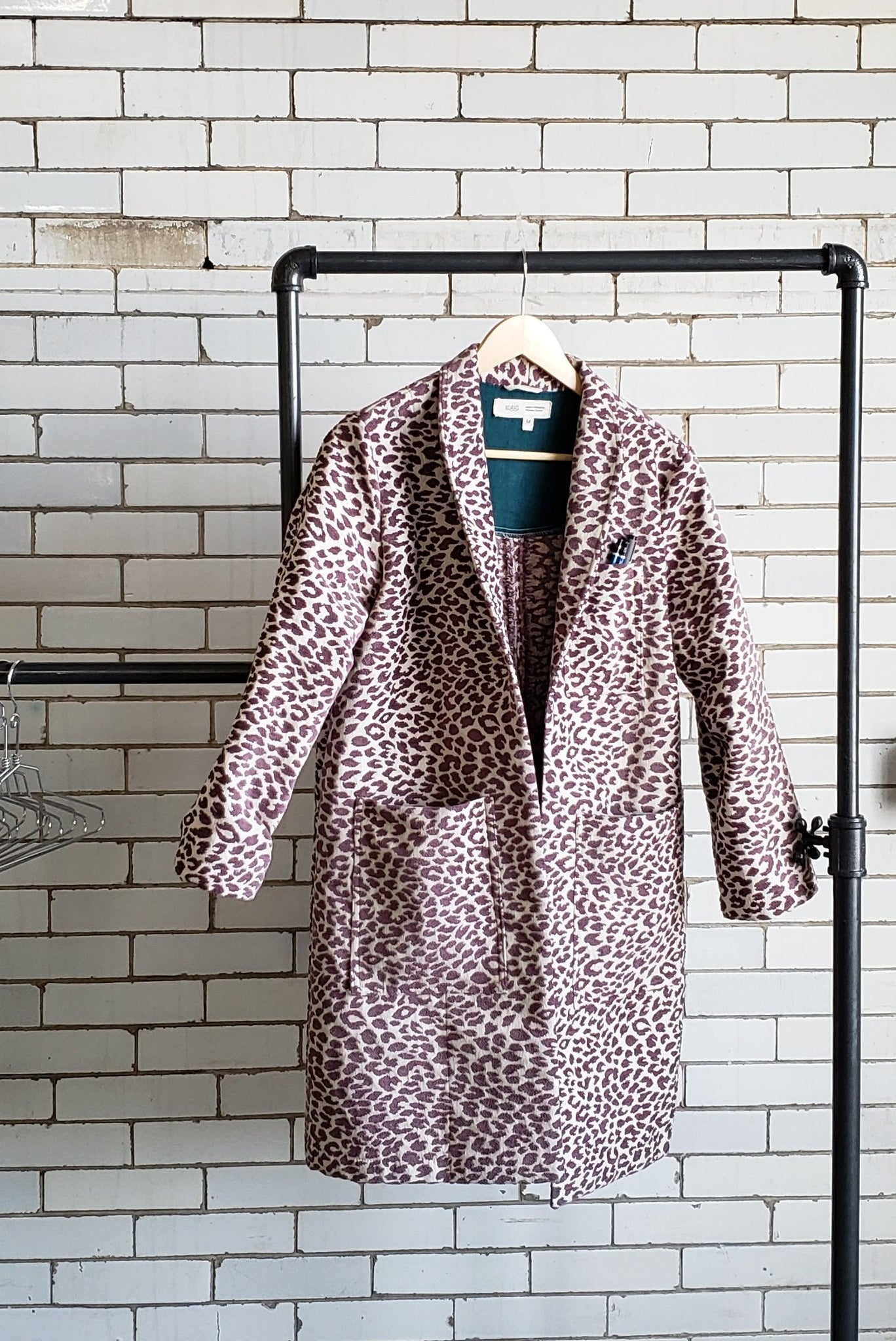 purple and cream women's coat hanging on a pipe clothing rack in front of a white brick wall