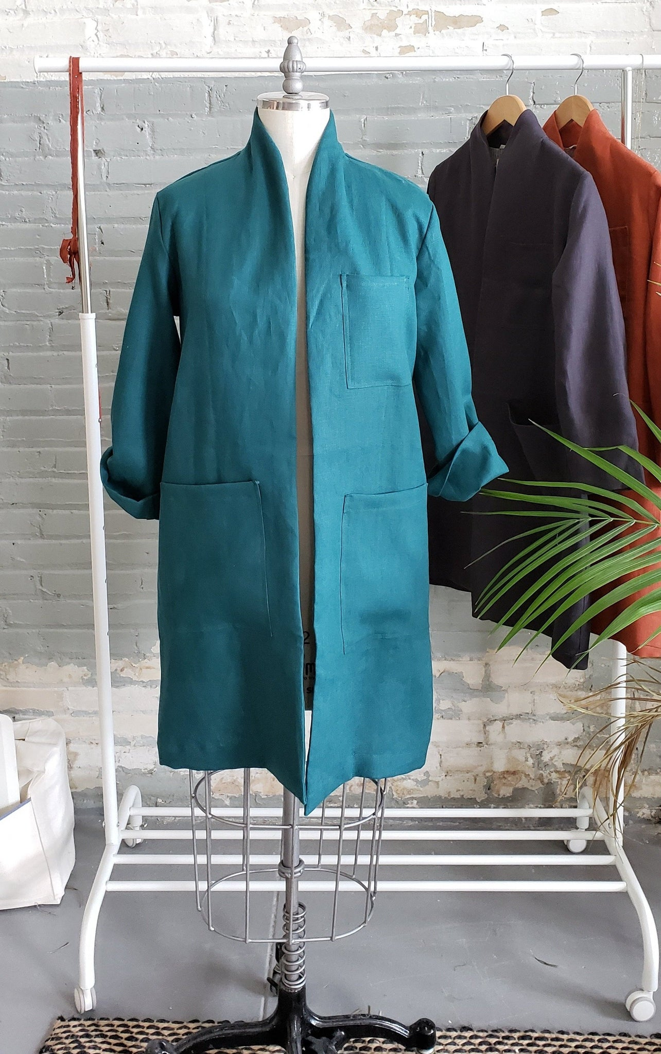 womens teal linen lab coats hanging on display
