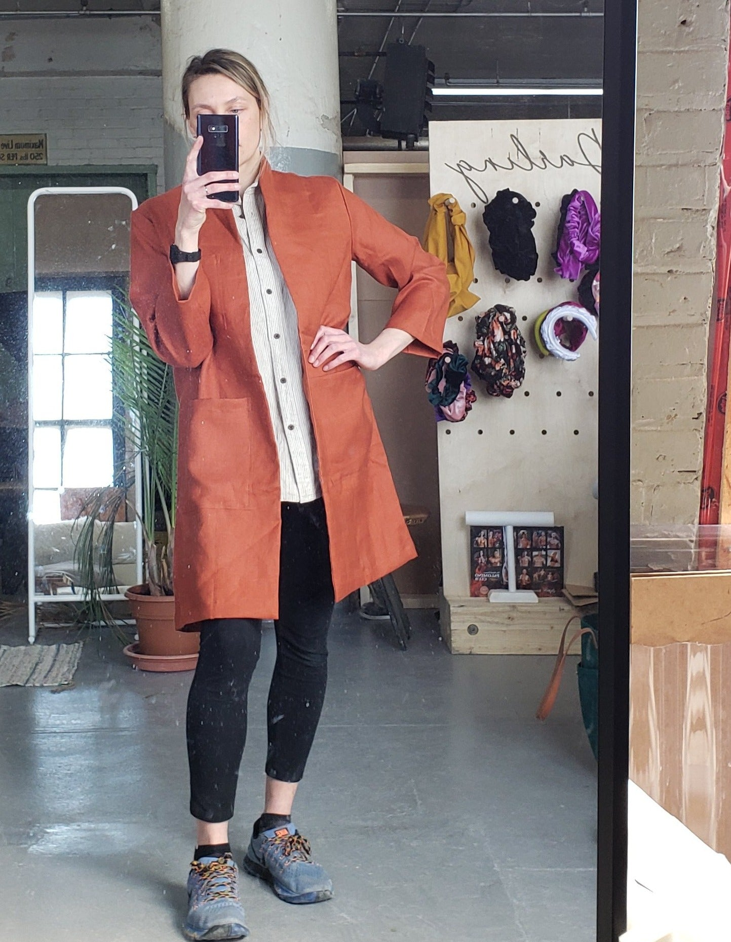 rust orange linen labcoat worn by a woman taking a selfie