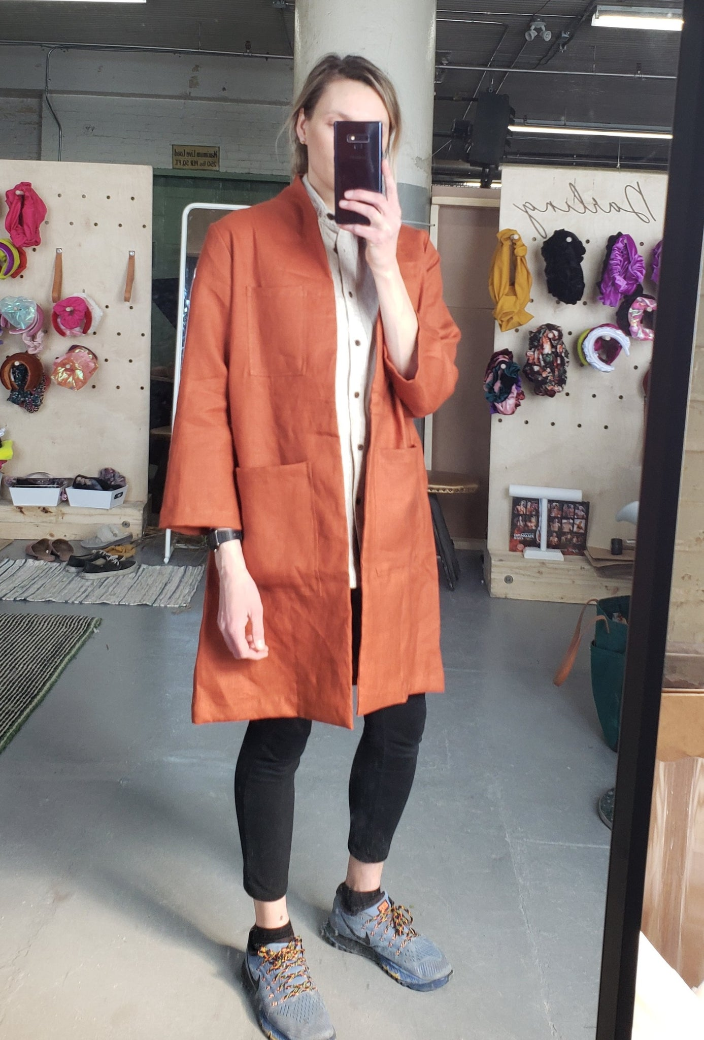 rust orange lab coat worn by a woman with leggings and runners holding a phone taking a picture in the mirror