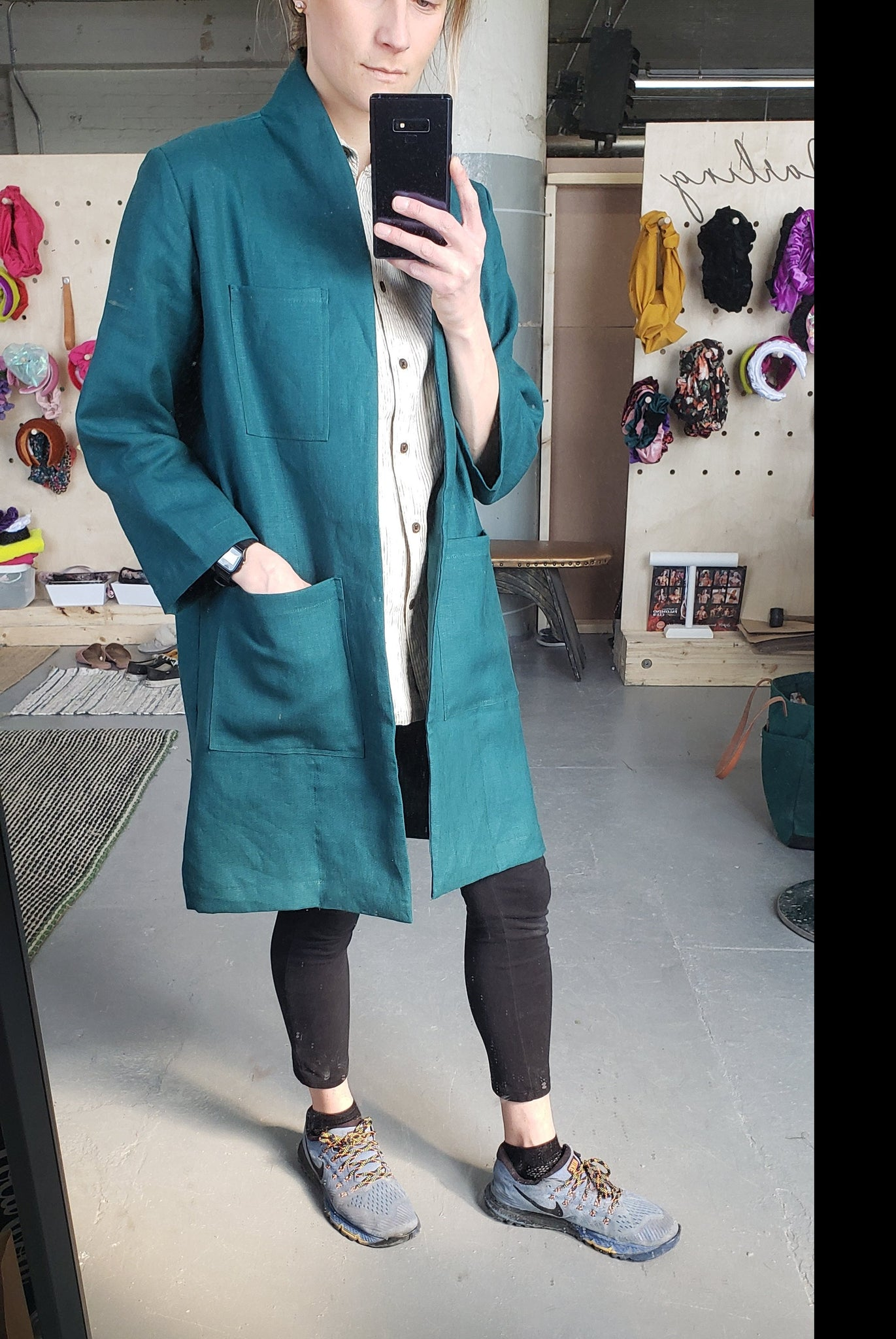woman wearing a teal linen lab coat with leggings and sneakers taking a selfie