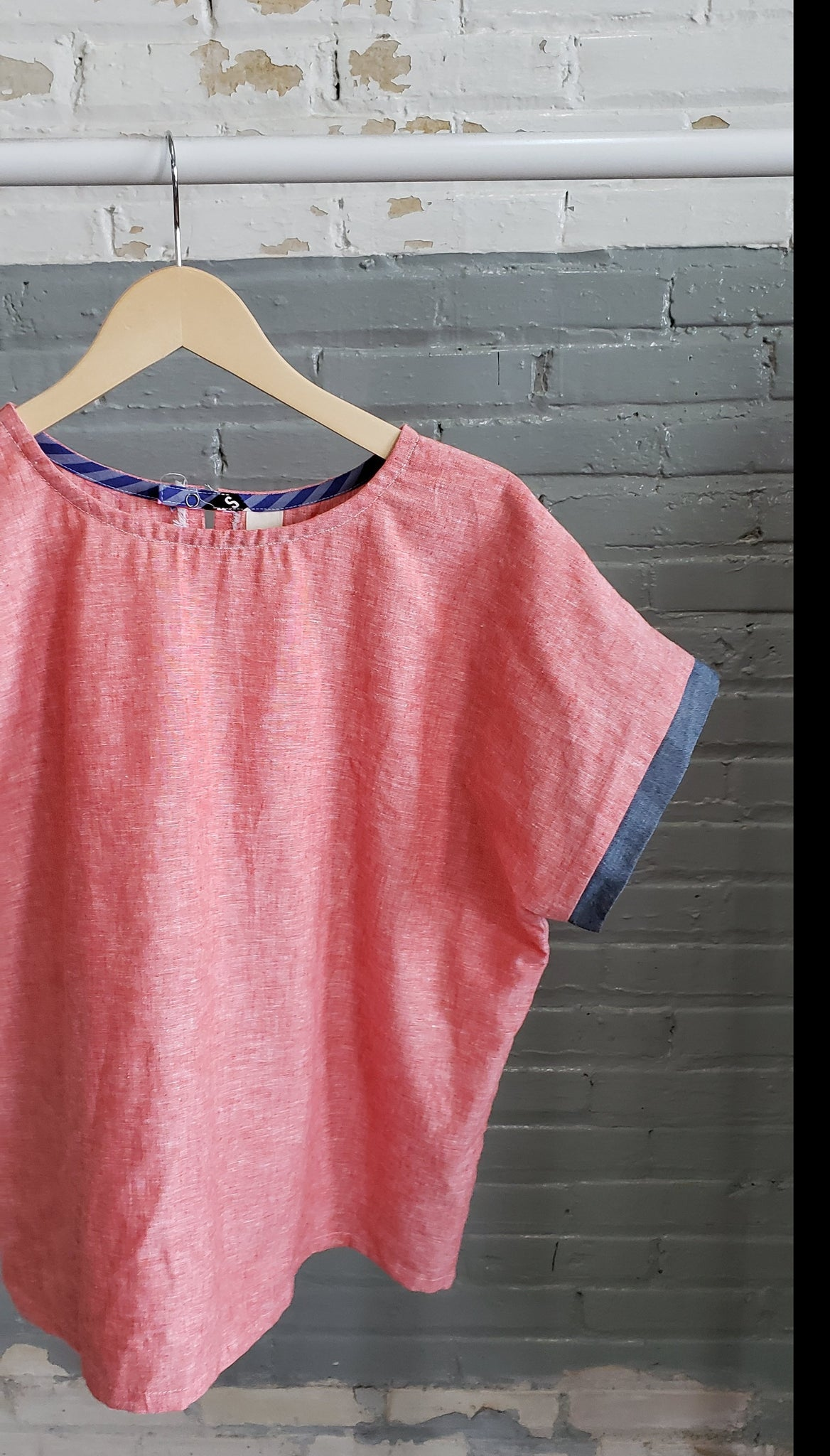 pink orange linen tee shirt blouse hanging on a clothing rack by a brick wall