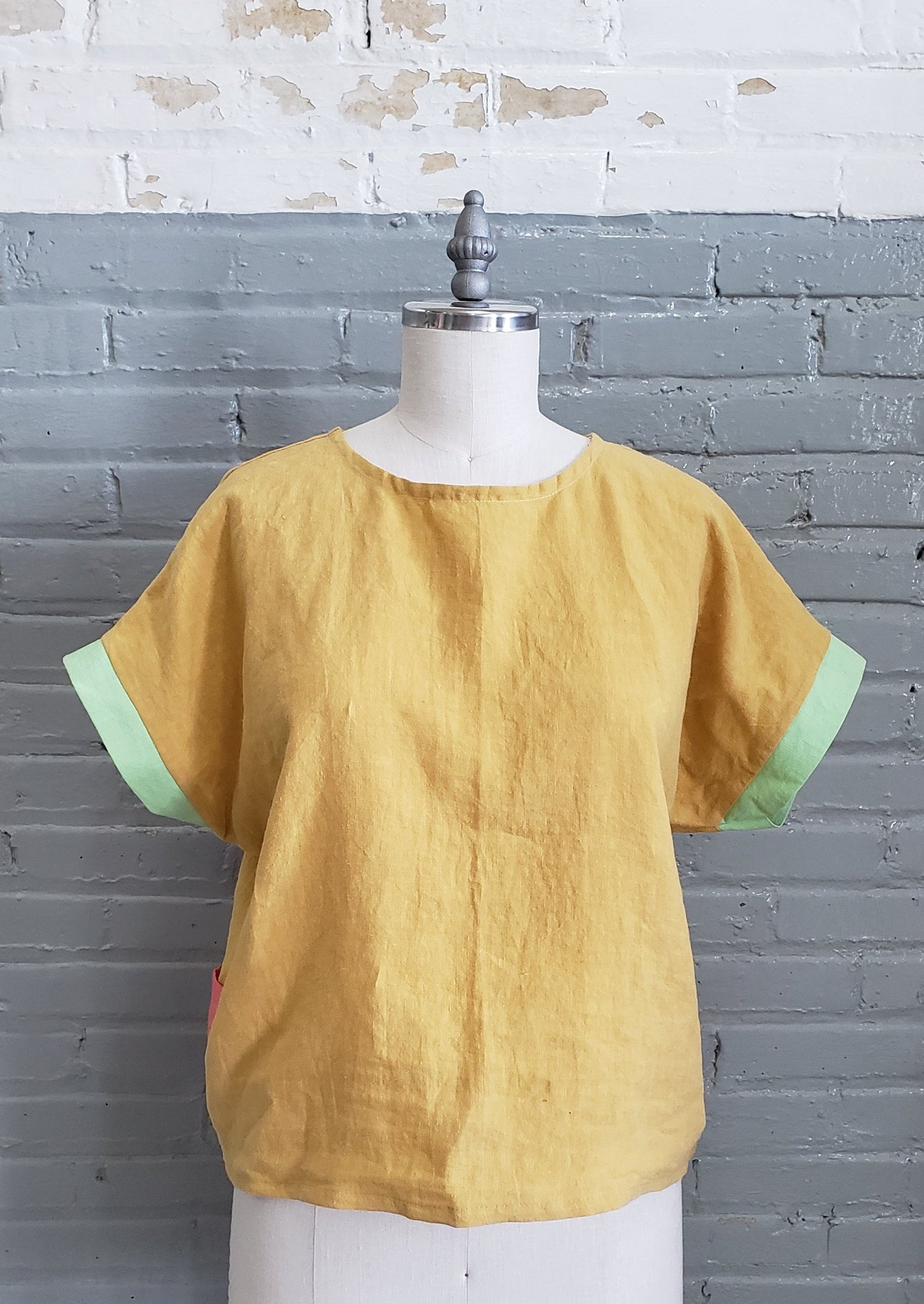 yellow linen tee shirt with green sleeve cuffs displayed on a dress form