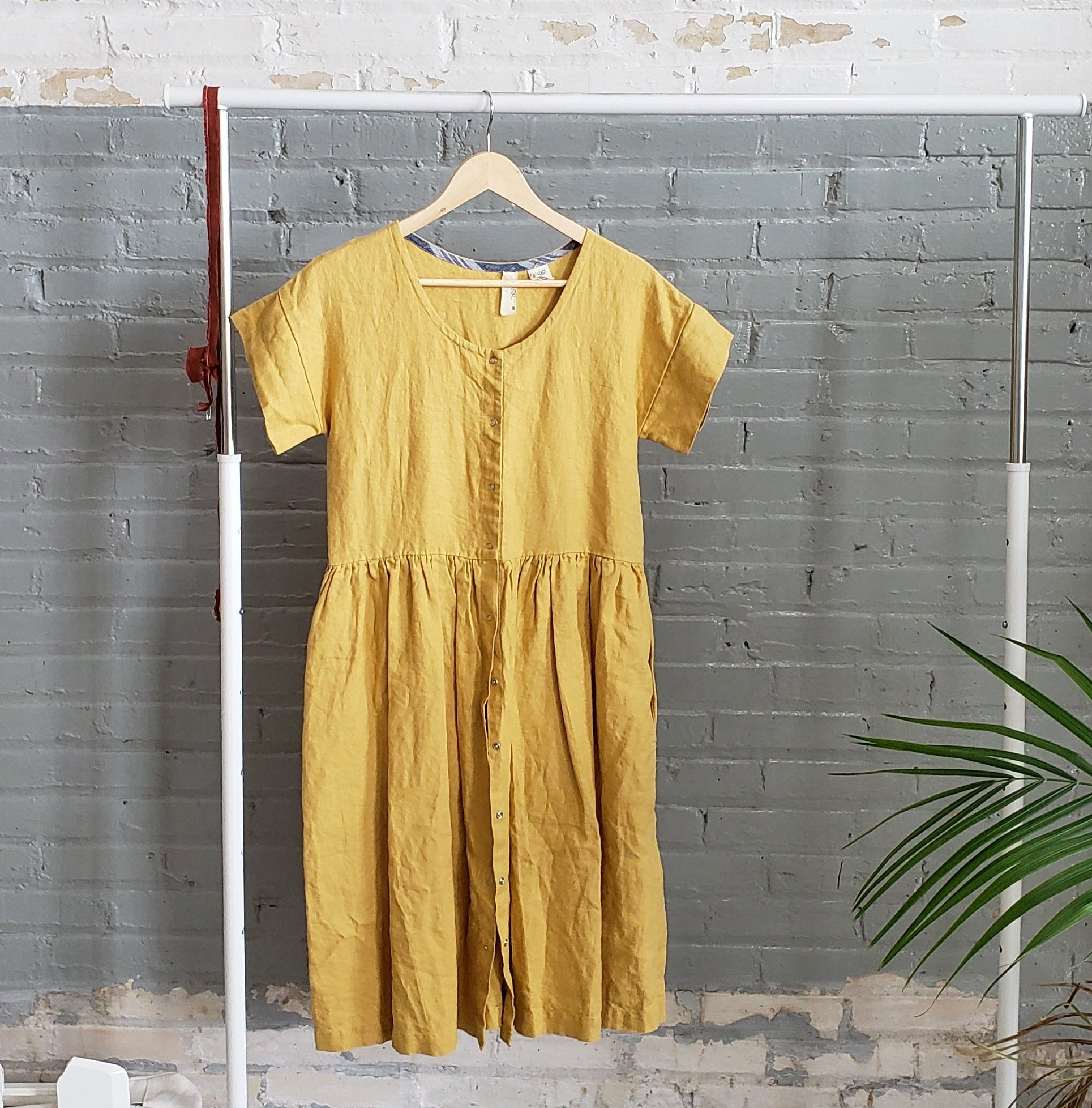 yellow linen short sleeve dress with gathered skirt hanging on a clothing rack beside a grey brick wall