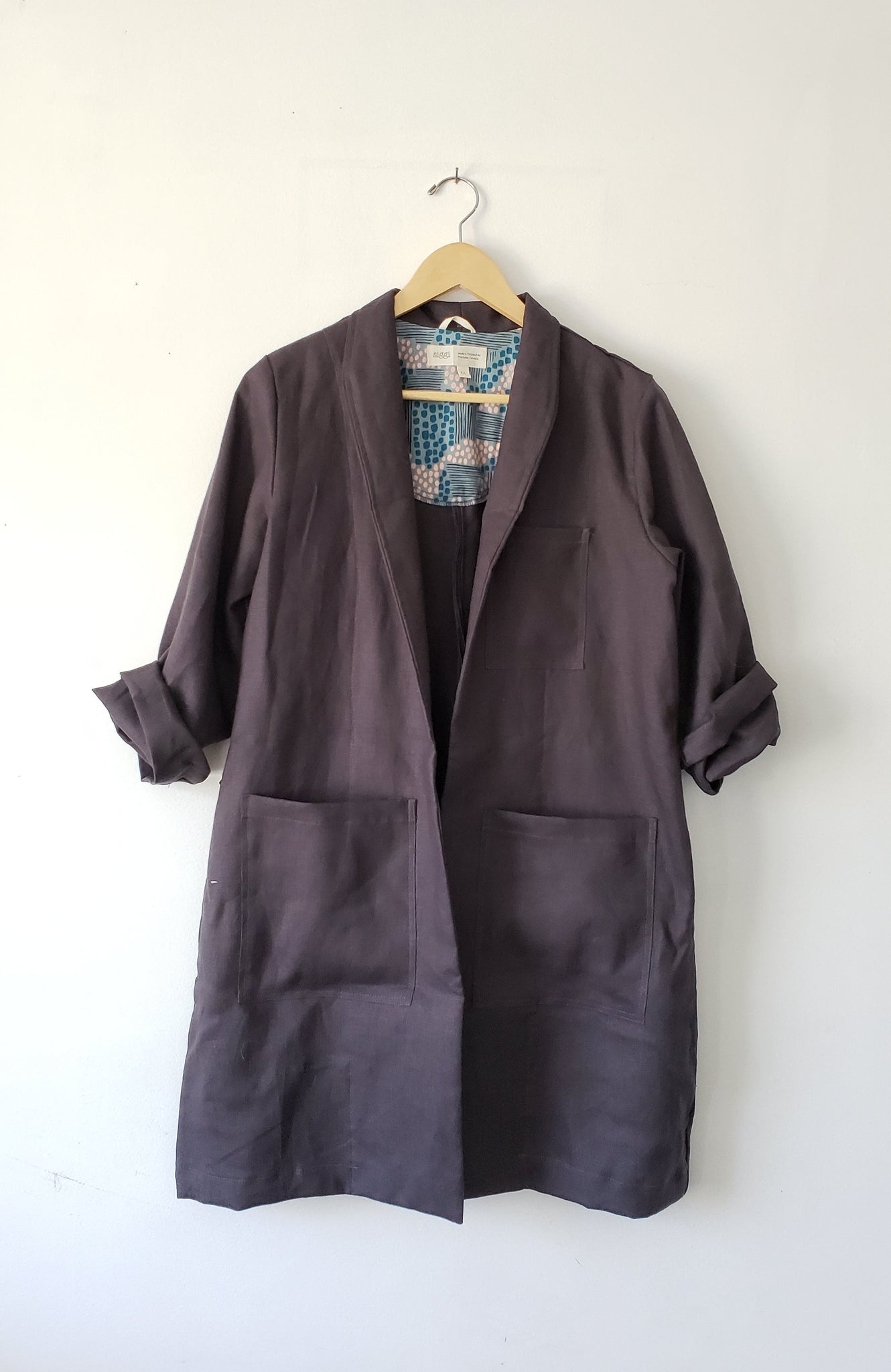charcoal grey linen labcoat hanging with sleeves rolled up