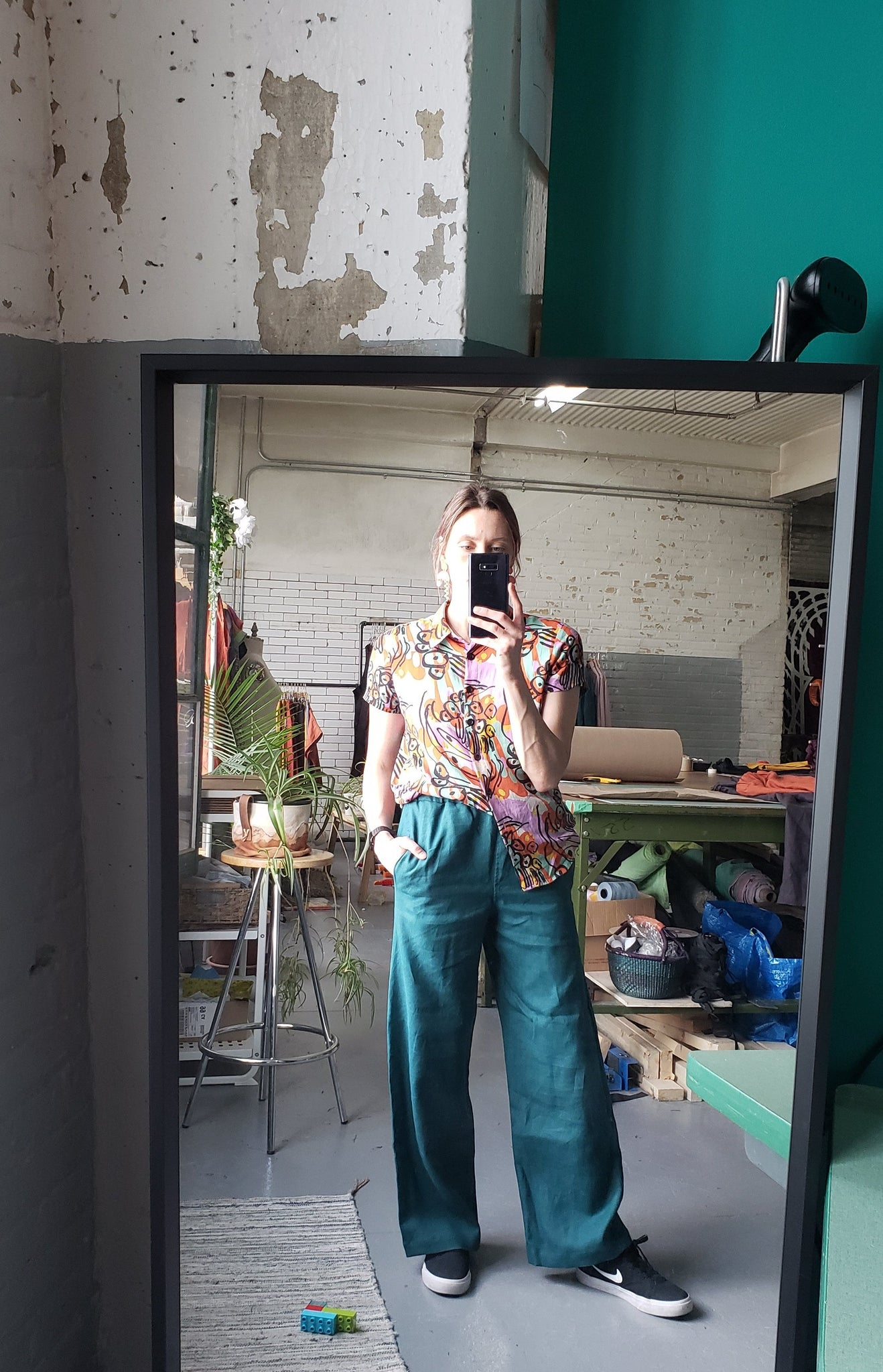 woman standing in mirror taking a picture wearing a brightly coloured shirt with teal linen pants and skate shoes