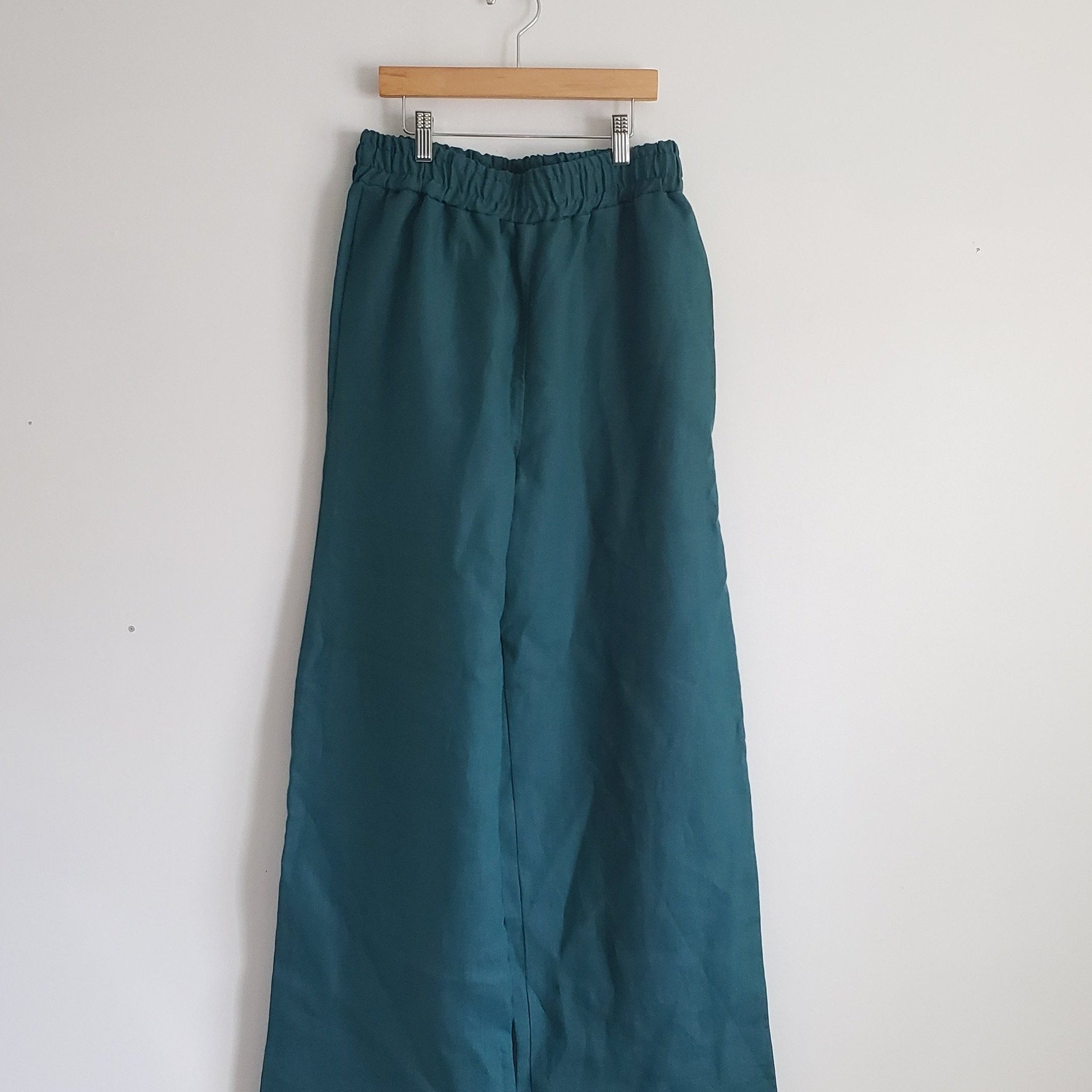 teal green blue linen pants hanging in a clothing hanger against a white wall backdrop