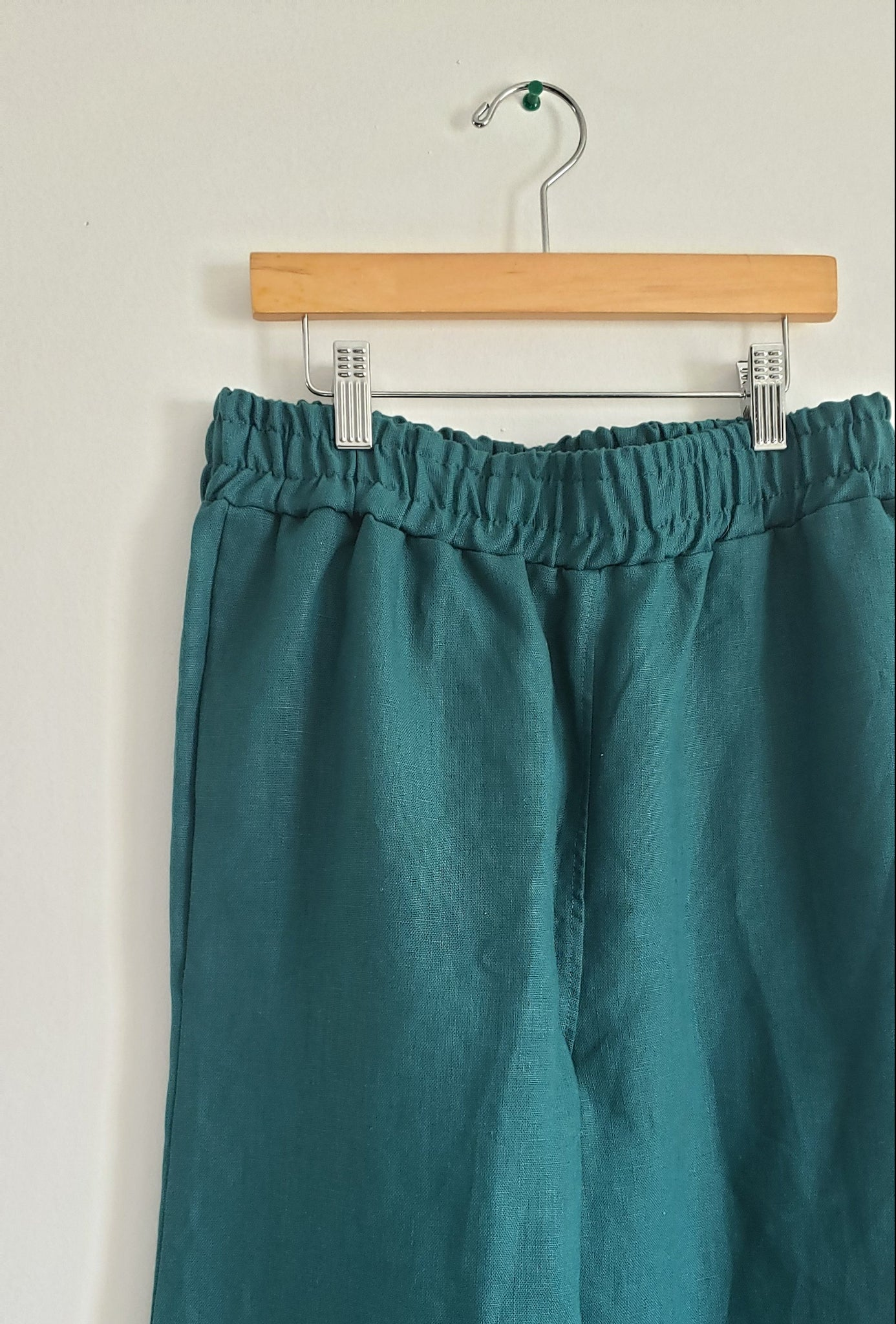 close up of teal green linen elastic waist pants hanging against a white wall