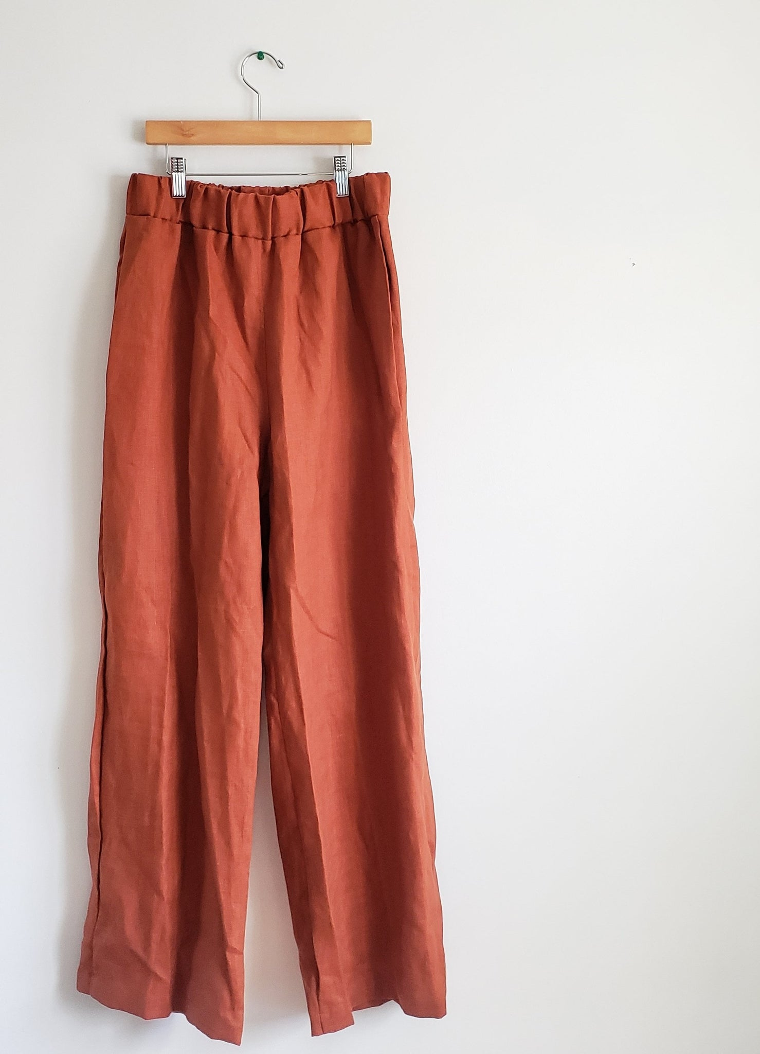 rust linen pants hanging on white wall