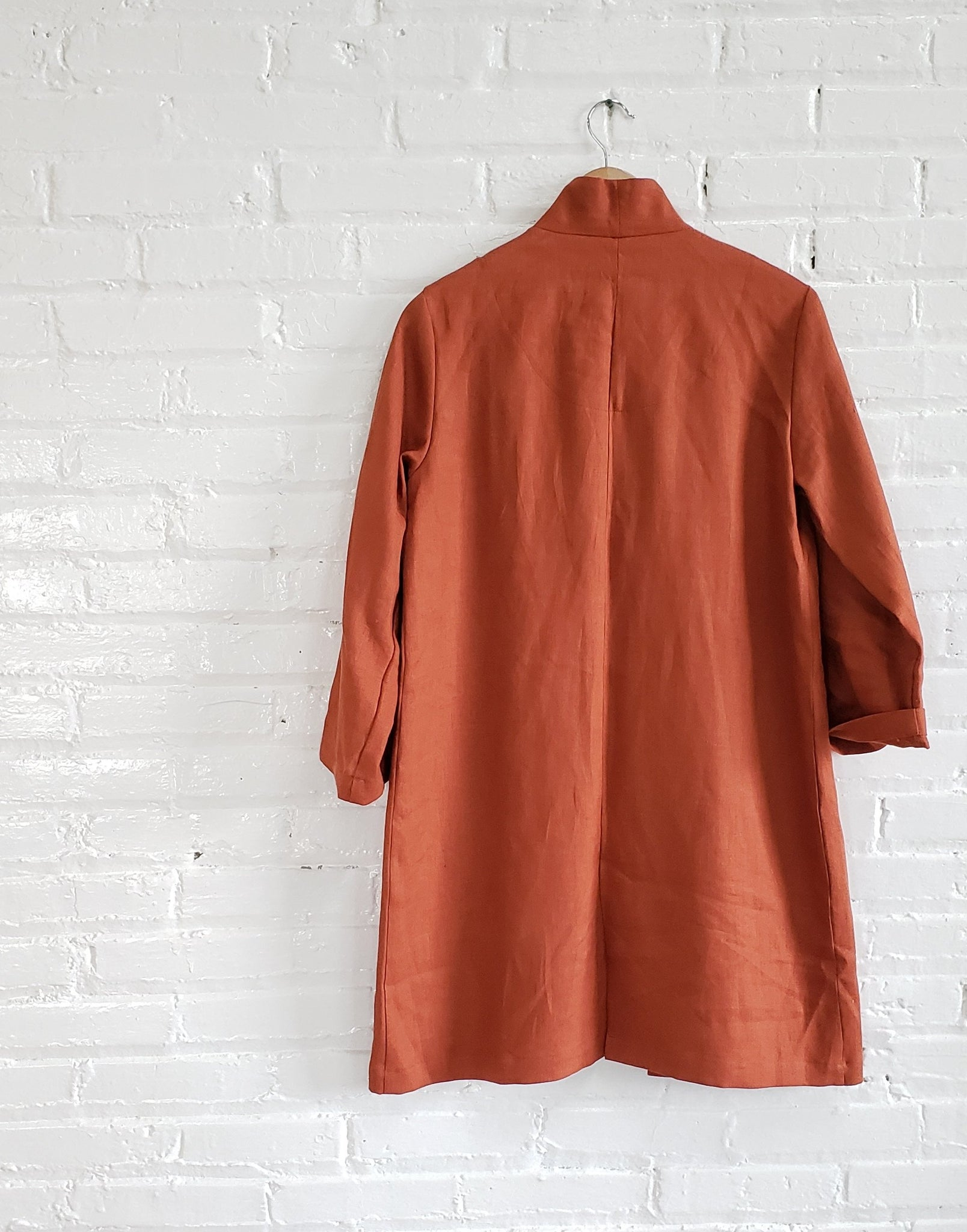 back view of a rust red orange linen labcoat hanging on a white brick wall