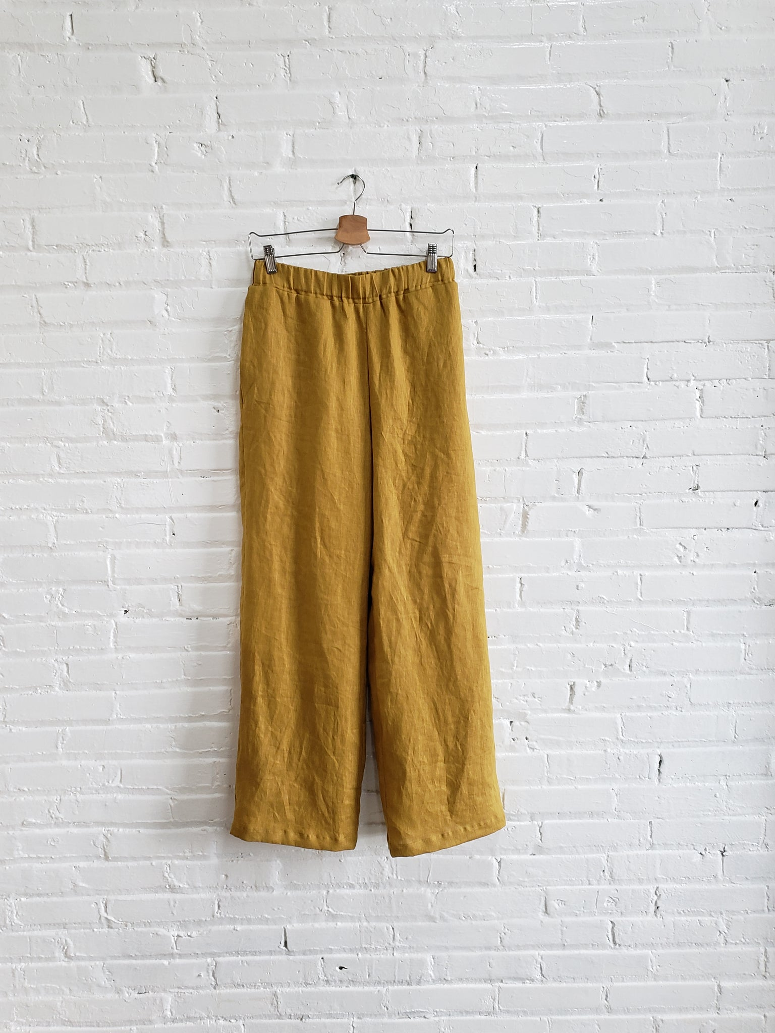 golden yellow linen pants hanging on a white brick wall