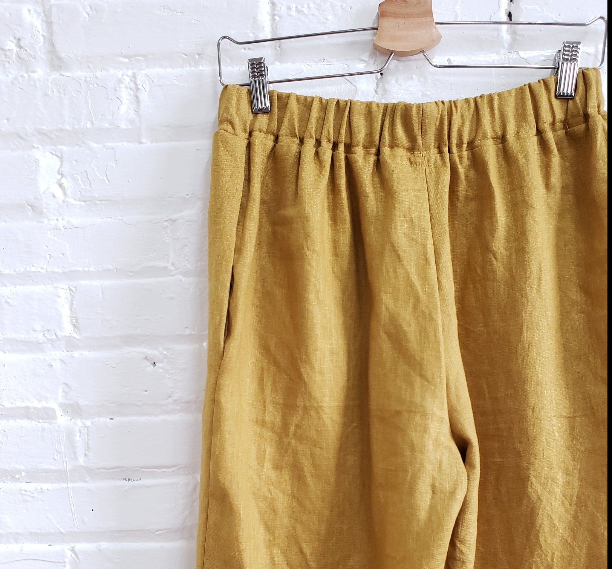 golden mustard yellow linen pants close up of waistband hanging on white brick wall