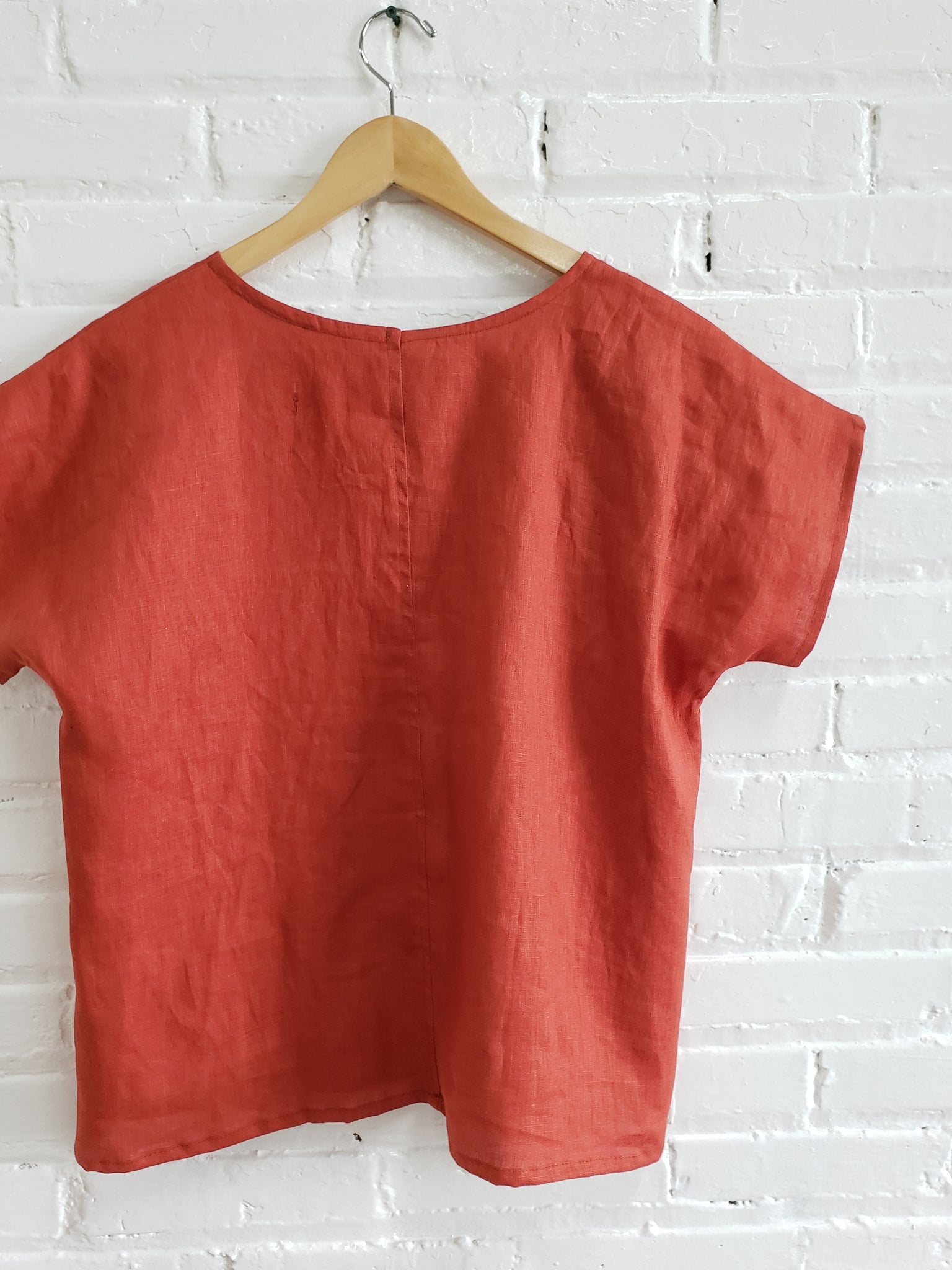 red linen womens tee hanging on white brick wall with a wooden hanger