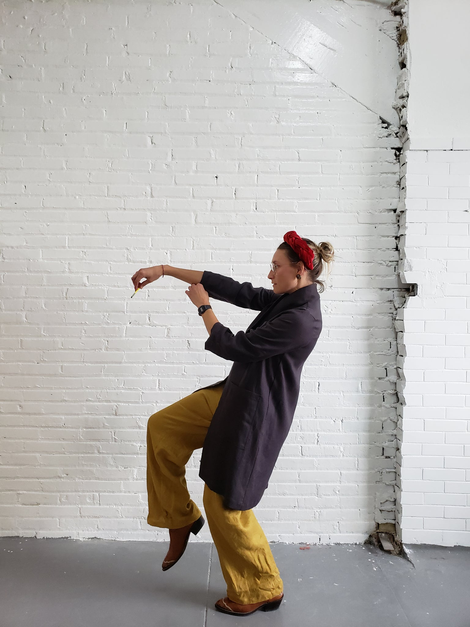 woman wearing charcoal labcoat with golden yellow linen pants editorial pose in front of a white brick wall