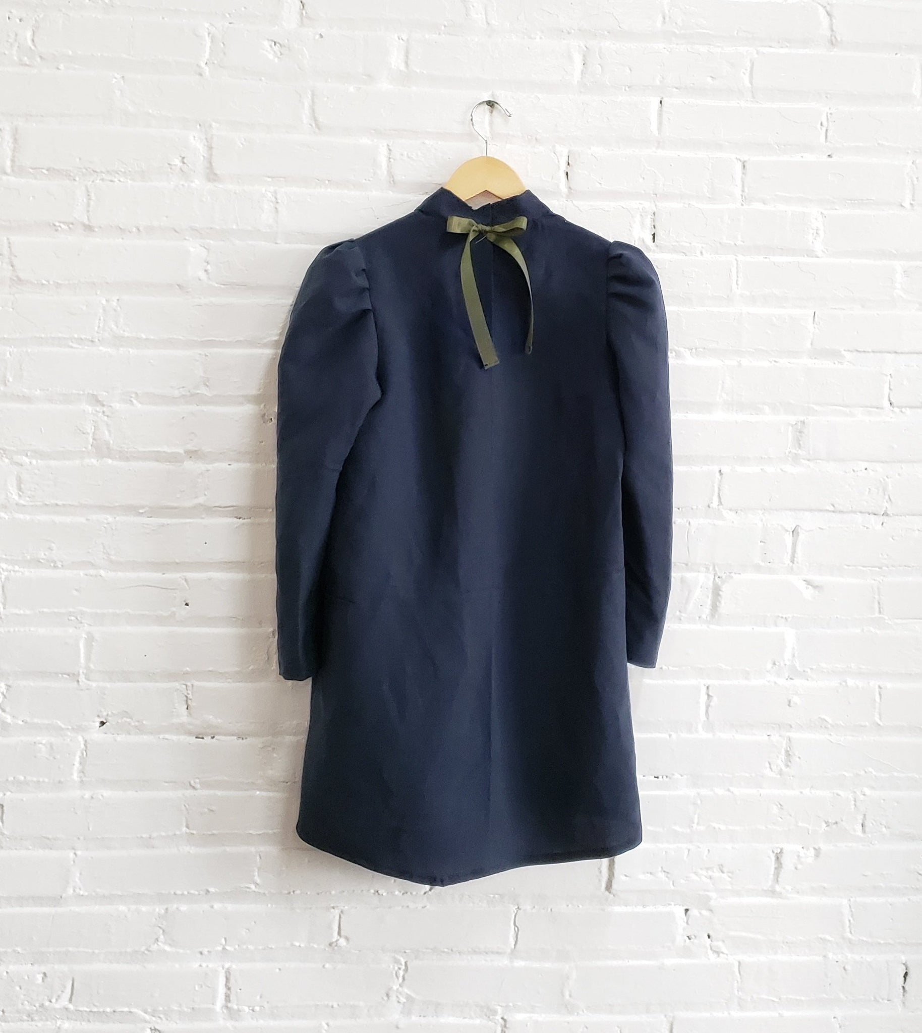 navy blue mini dress with puffy sleeves and olive green ribbon tie hanging on white brick wall