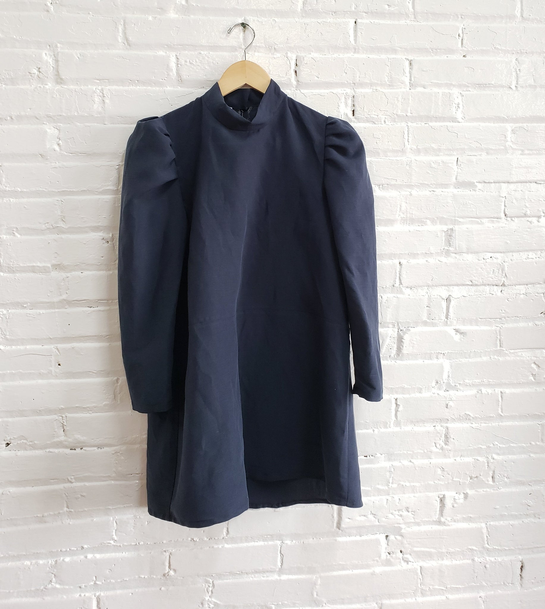 navy blue mini dress with puffy sleeves and mock neck hanging on white brick wall