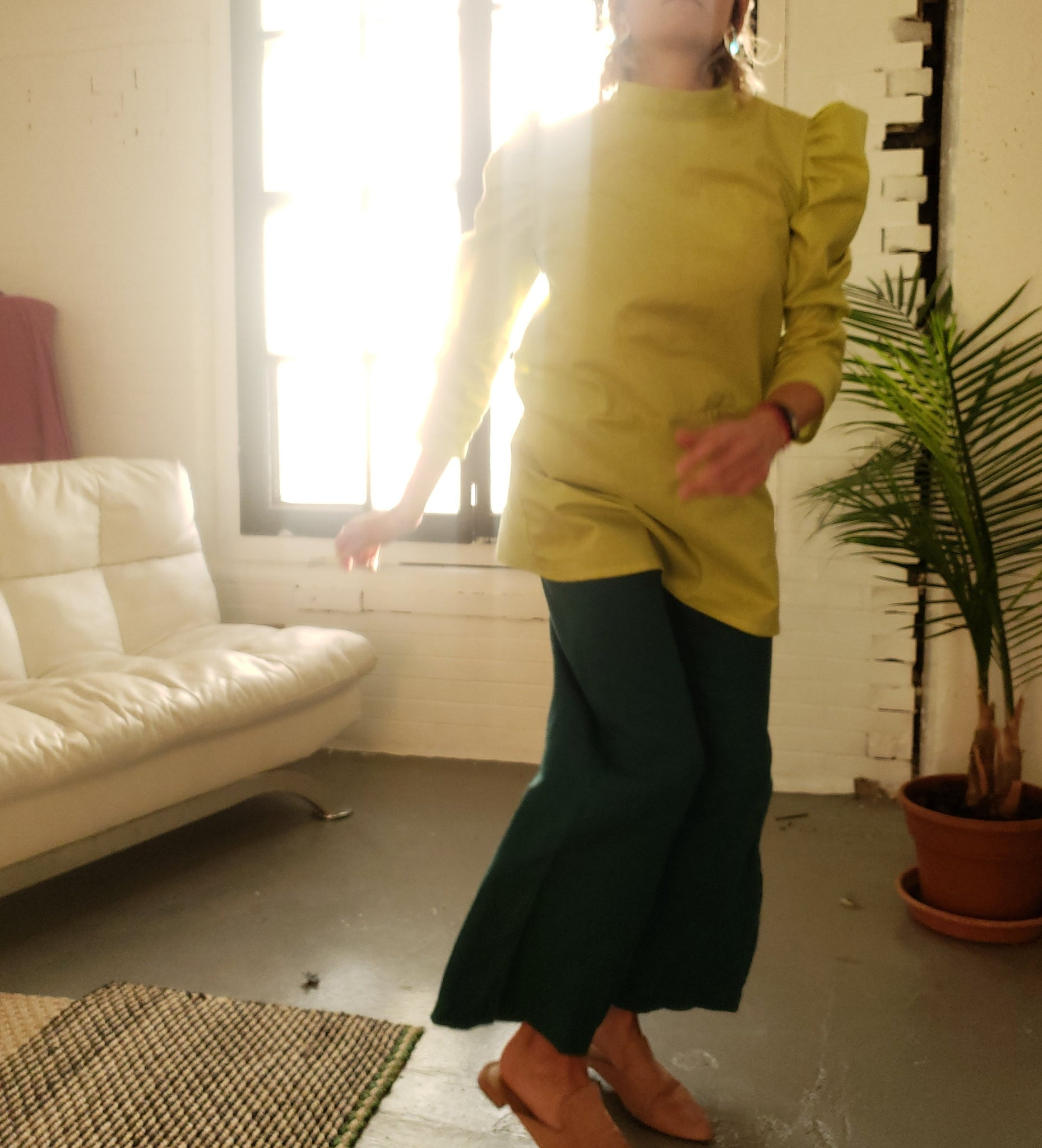 woman wearing green puffy sleeve dress with wide teal pants, dancing in the morning light coming in from large brick warehouse windows