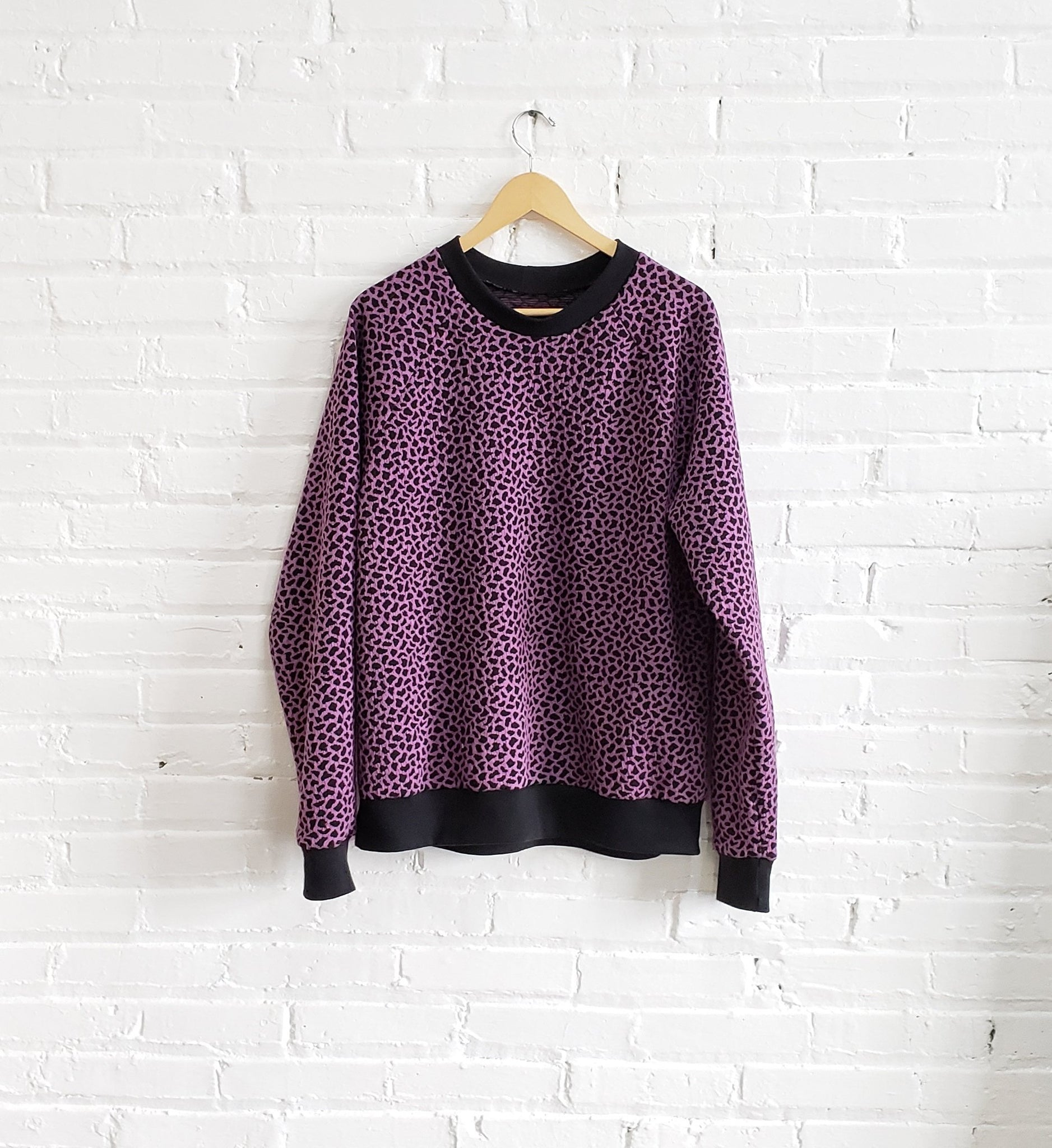 purple black speckled sweatshirt hanging on a white brick wall