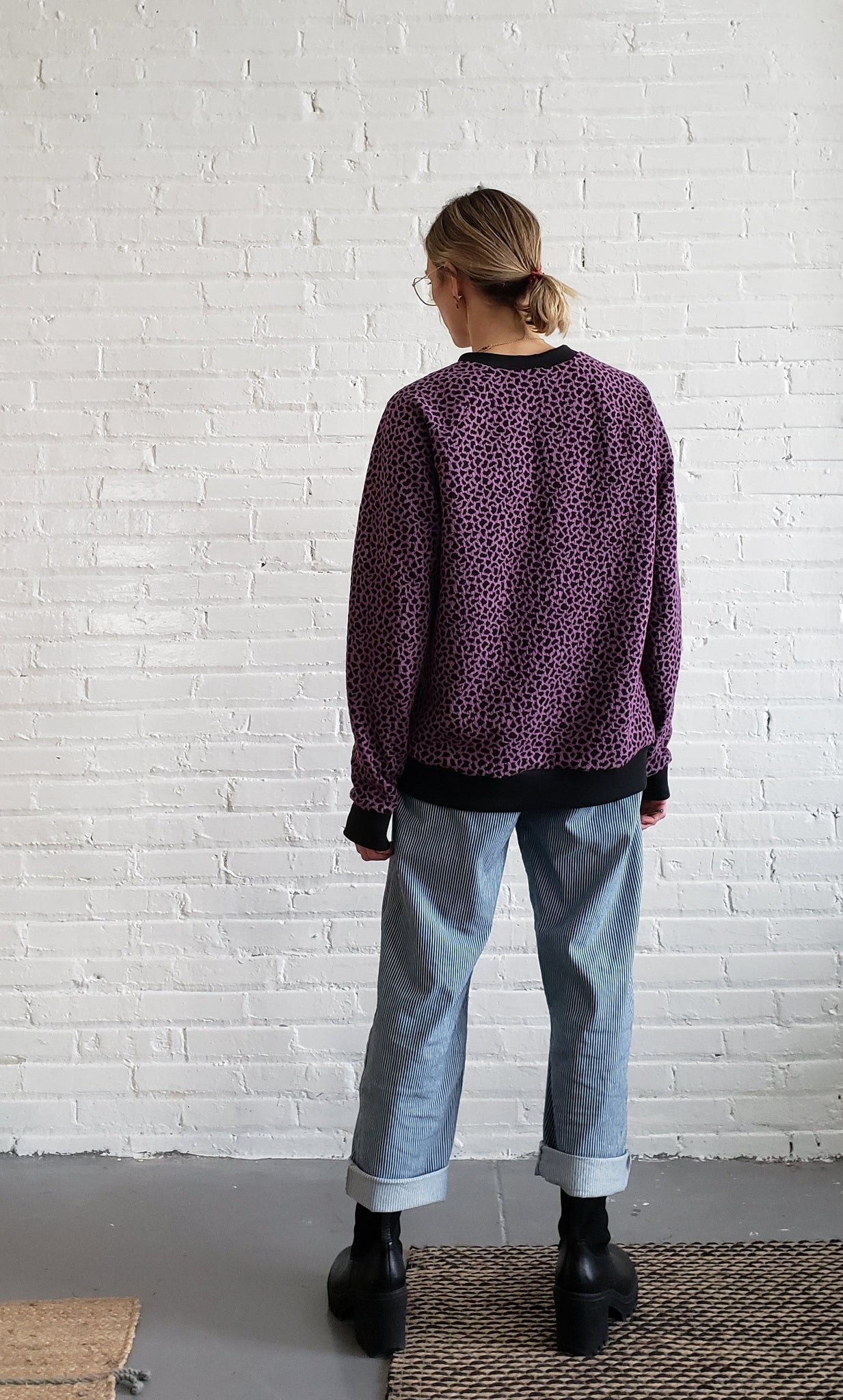 woman wearing purple and black patterned sweatshirt with blue jeans and black boots, facing away from camera