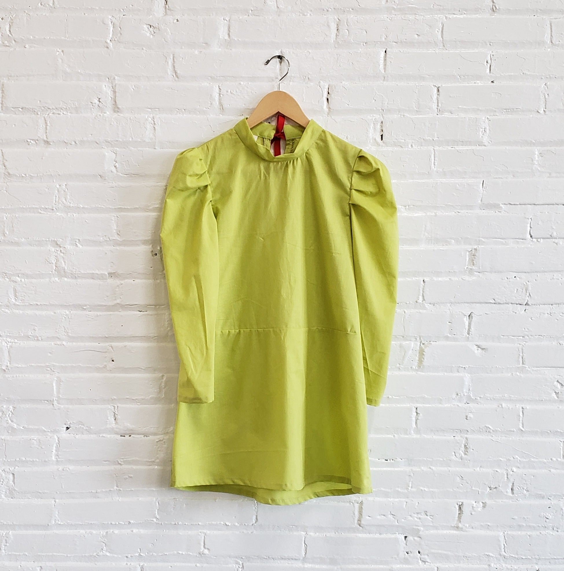 line green mini dress with puffy full length sleeves, displayed hanging against a white brick wall