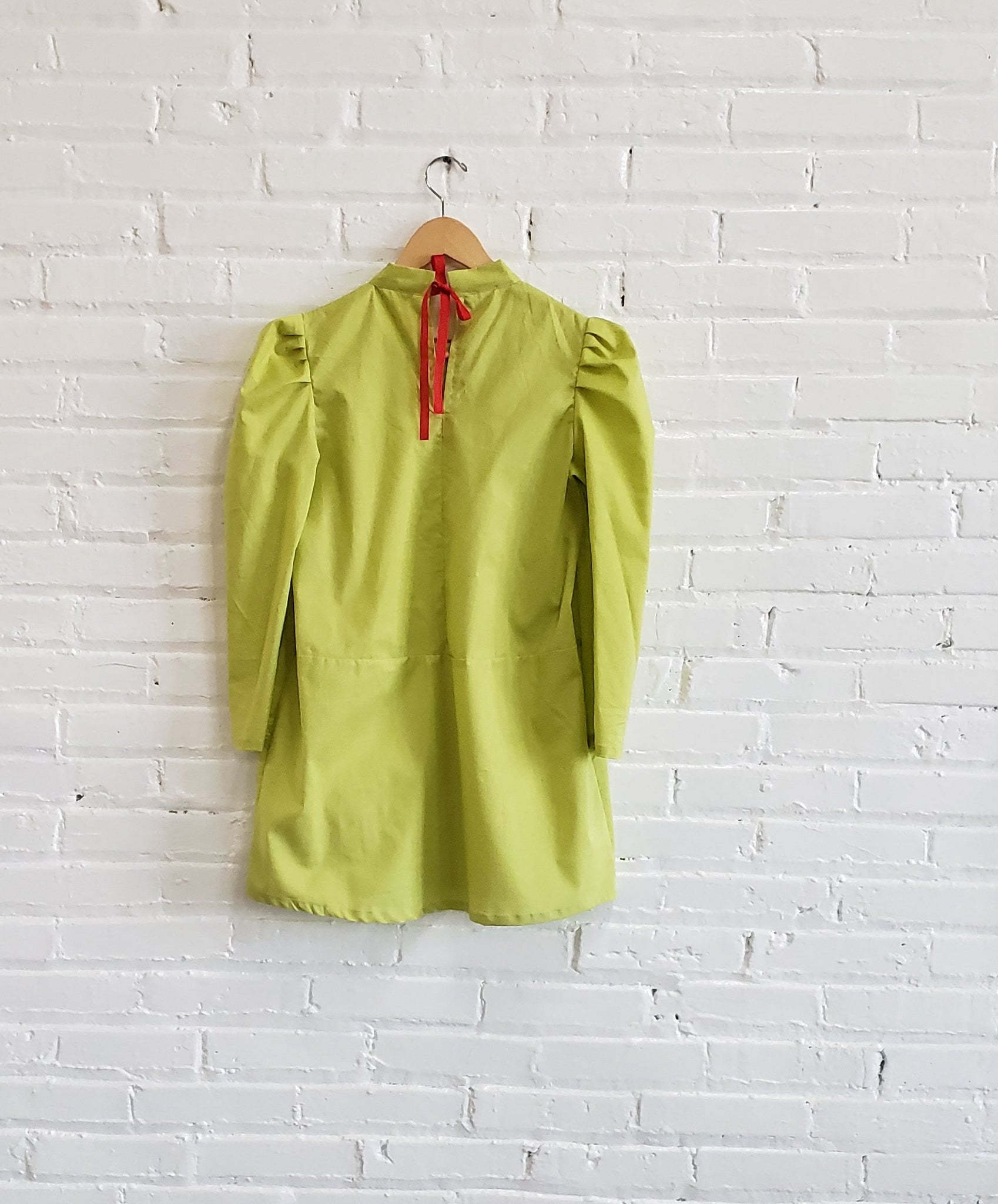 lime green mini dress with puffy sleeves and poppy red ribbon tie, displayed hanging against a white brick wall