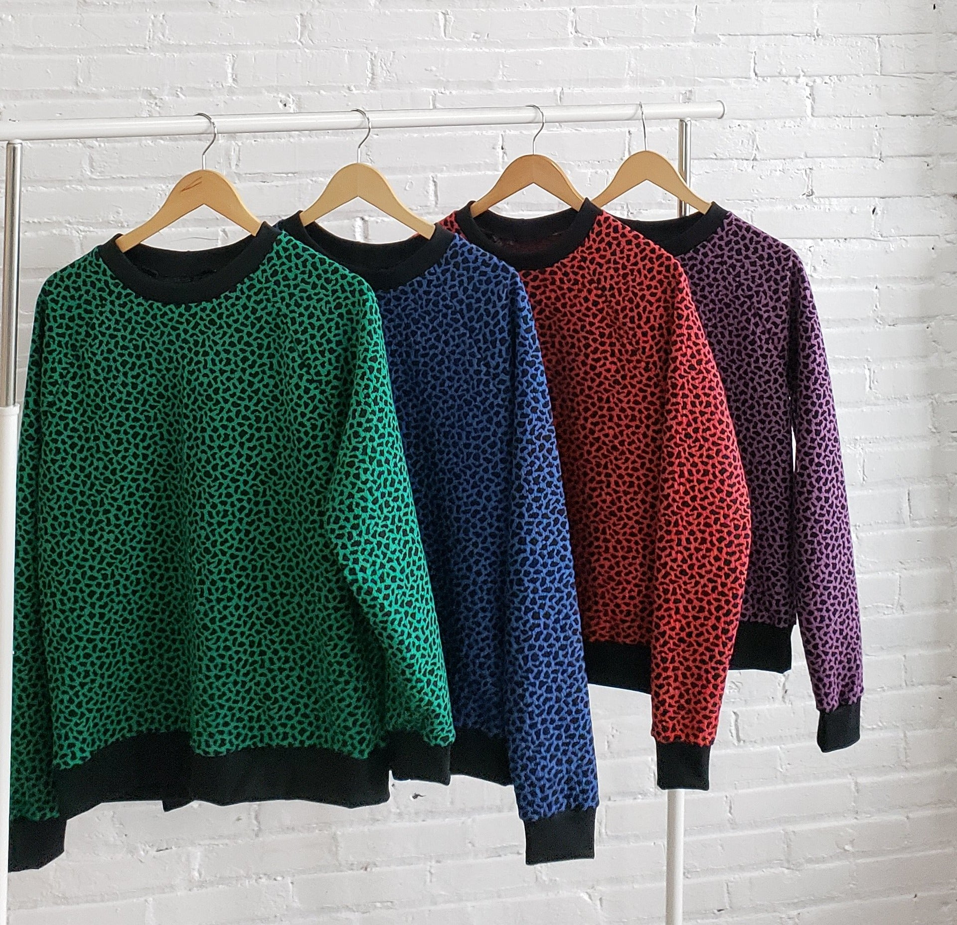 sweatshirts hanging on a clothing rack in order of green, blue, red and purple with black cheetah spots and cuffs
