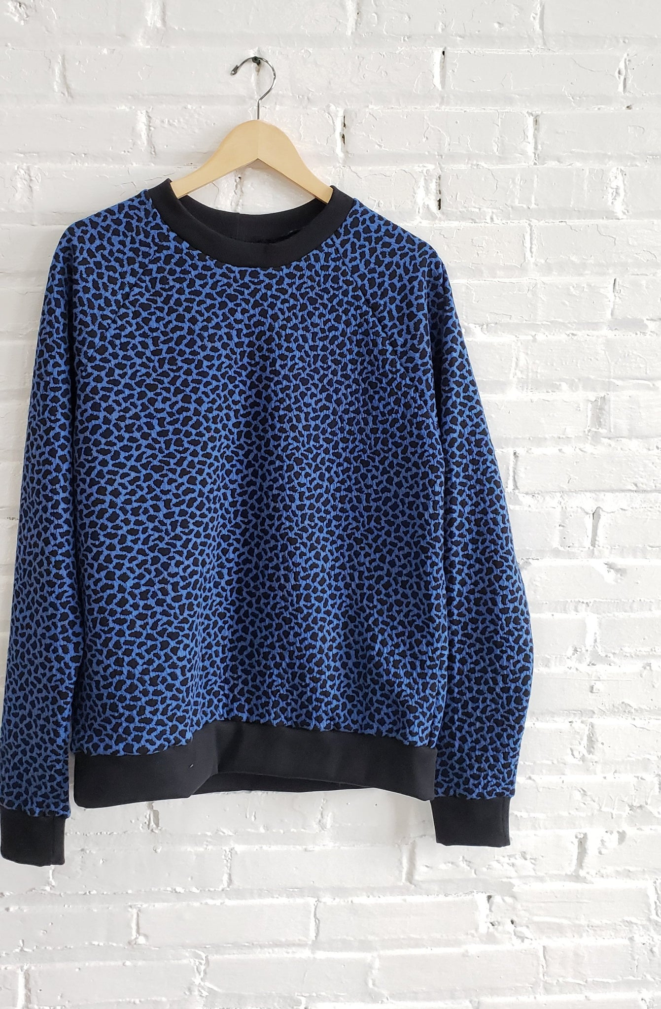 bright blue sweatshirt with black cuffs and cheetah spots, displayed on wooden hanger against white brick wall