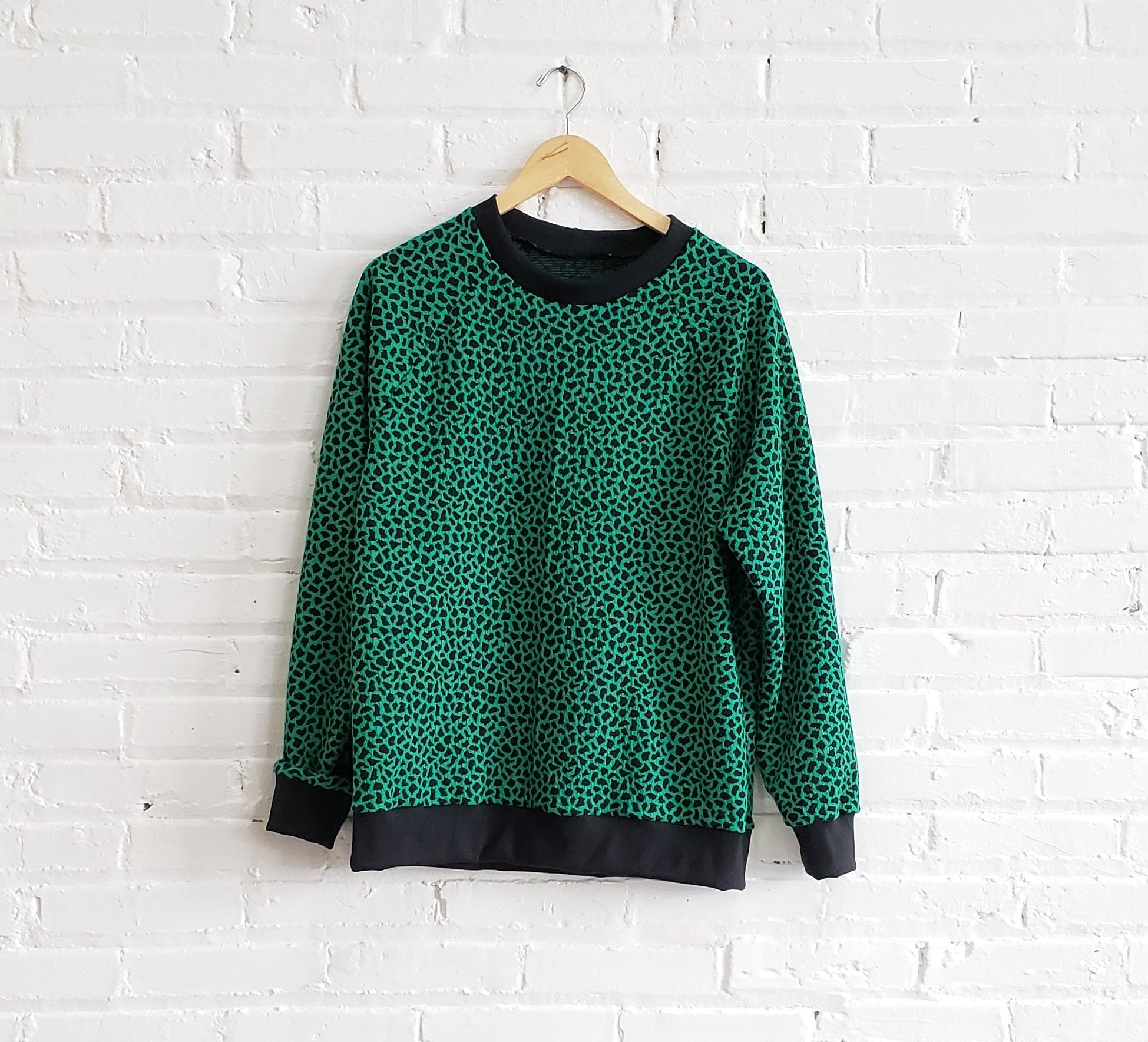 bright green sweatshirt with black cheetah spots and rib cuffs, displayed on wooden hanger against white brick wall