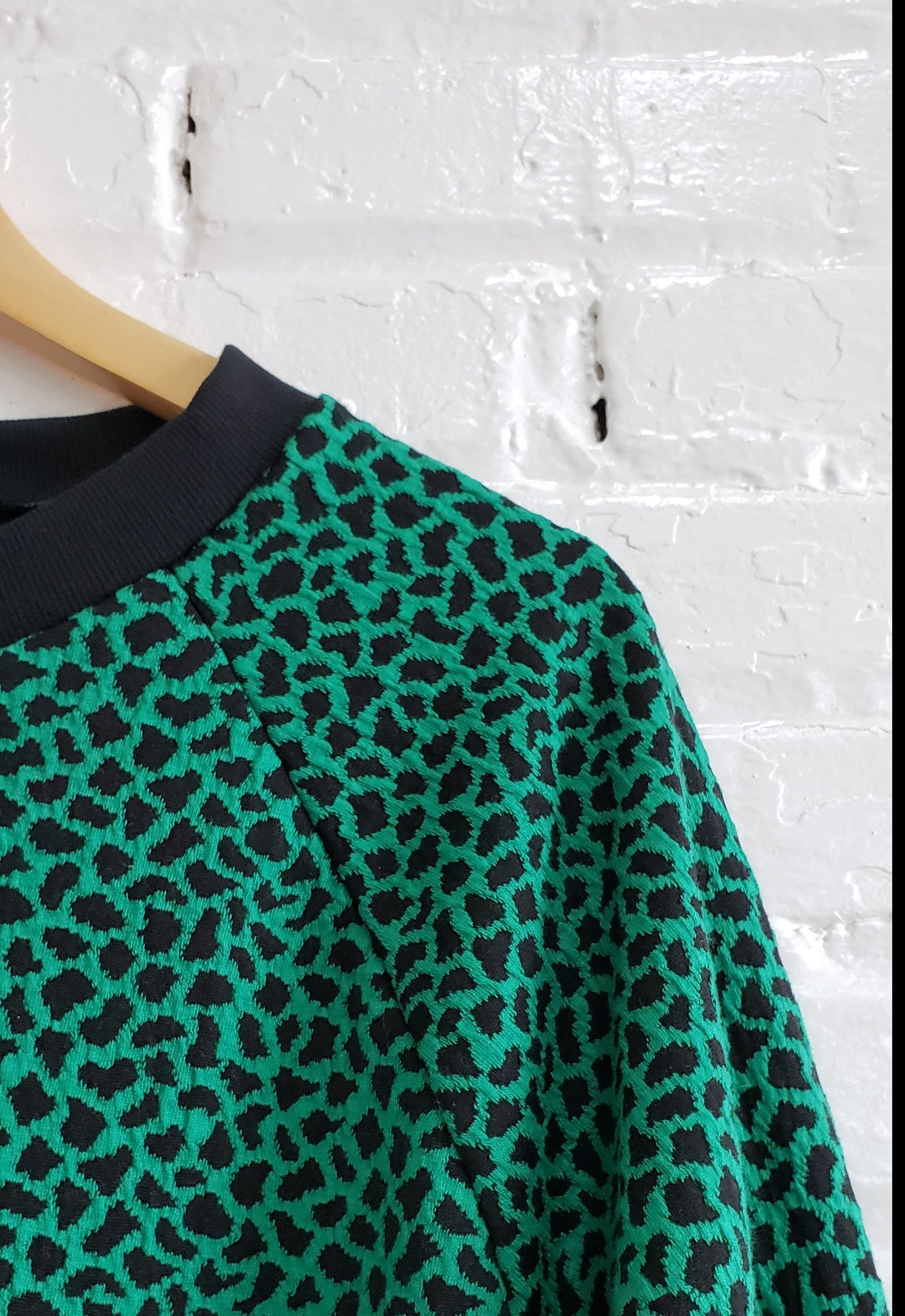 close up of bright green with black speckles sweatshirt, showing black rib neckband and raglan sleeve detail