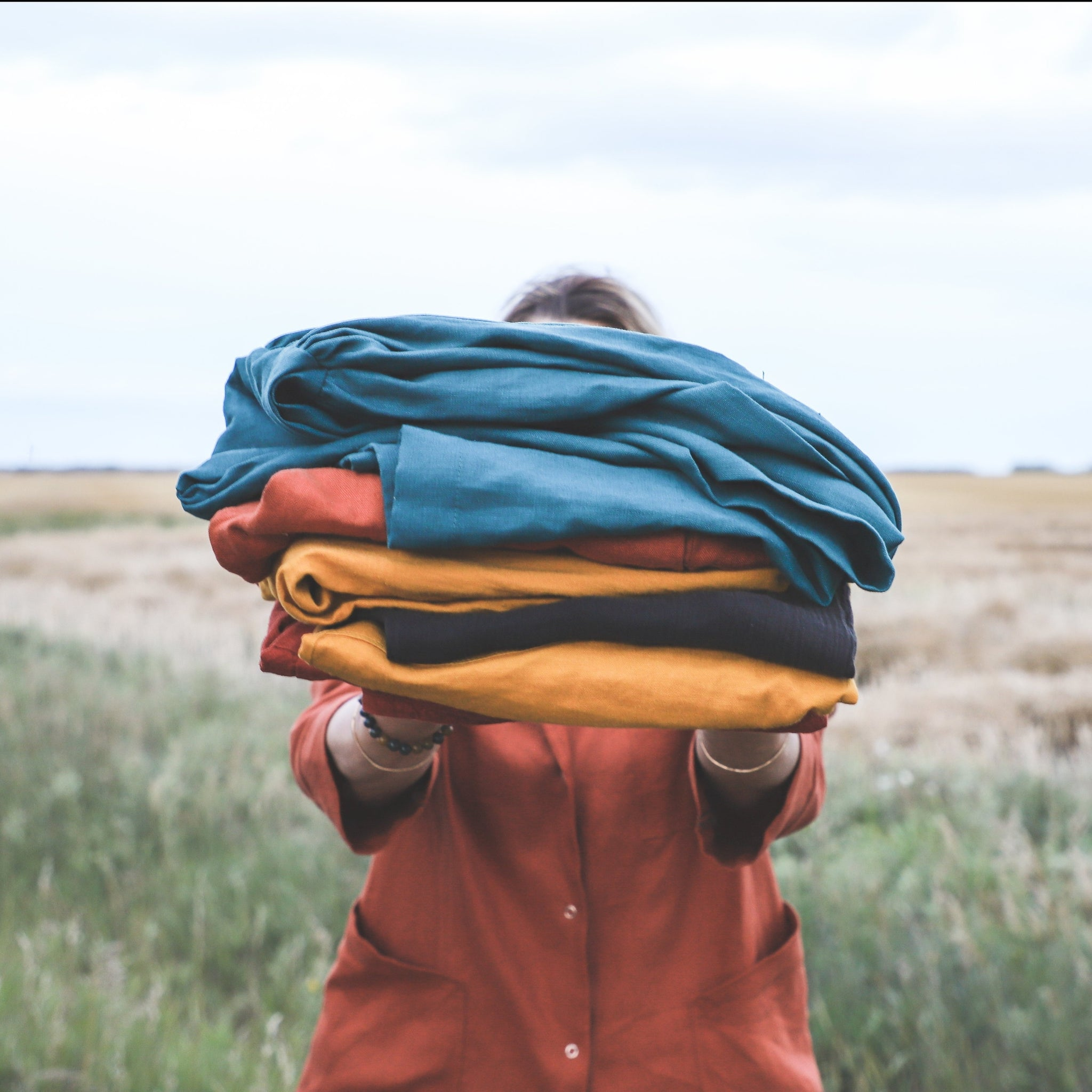 model holding in front of her a pile of folded linen clothes standing in a field