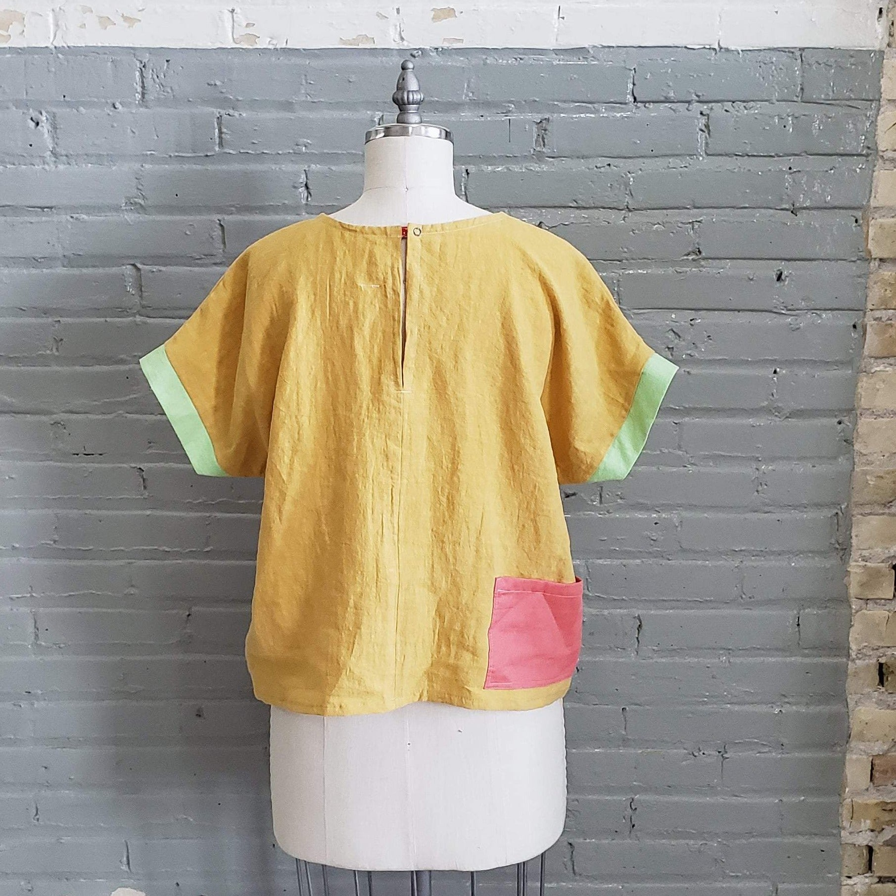 yellow linen tee shirt with pink pocket displayed on a dress from as shown from the back