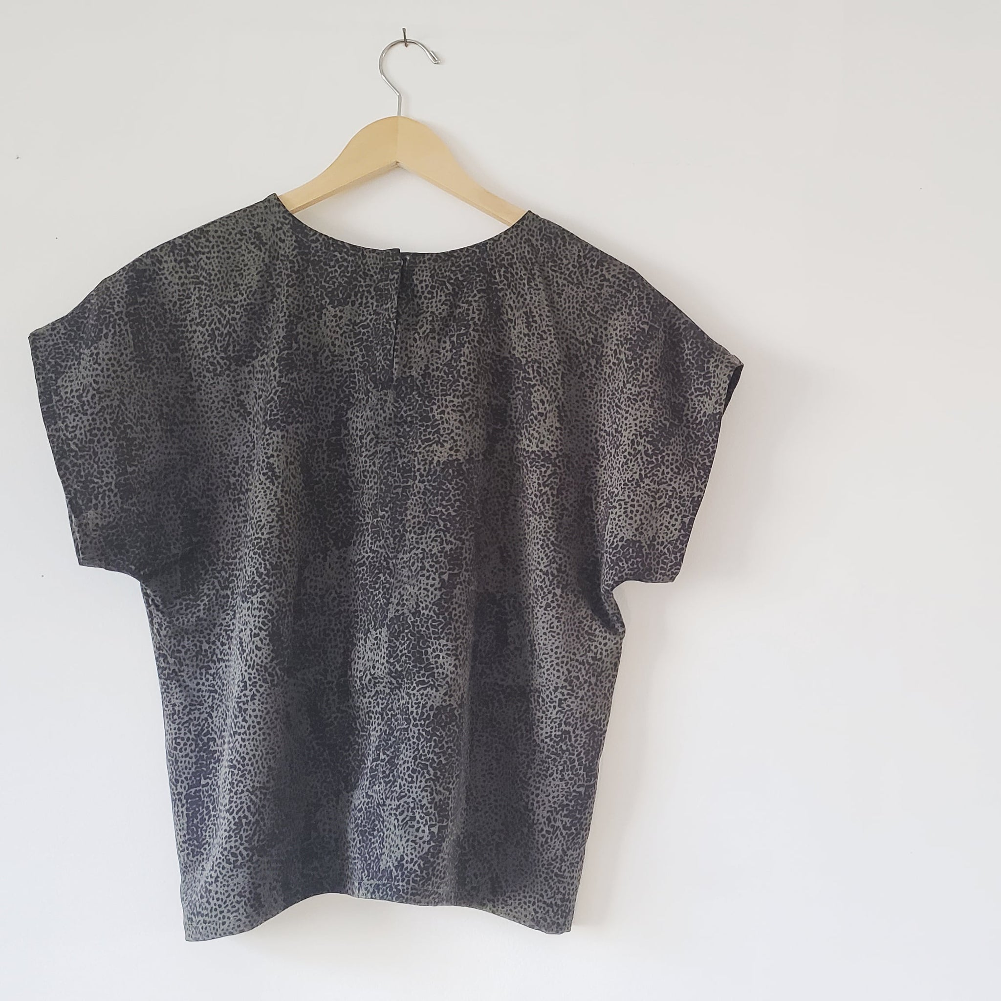 olive green with small black cheetah spots tee shirt hanging on a wall