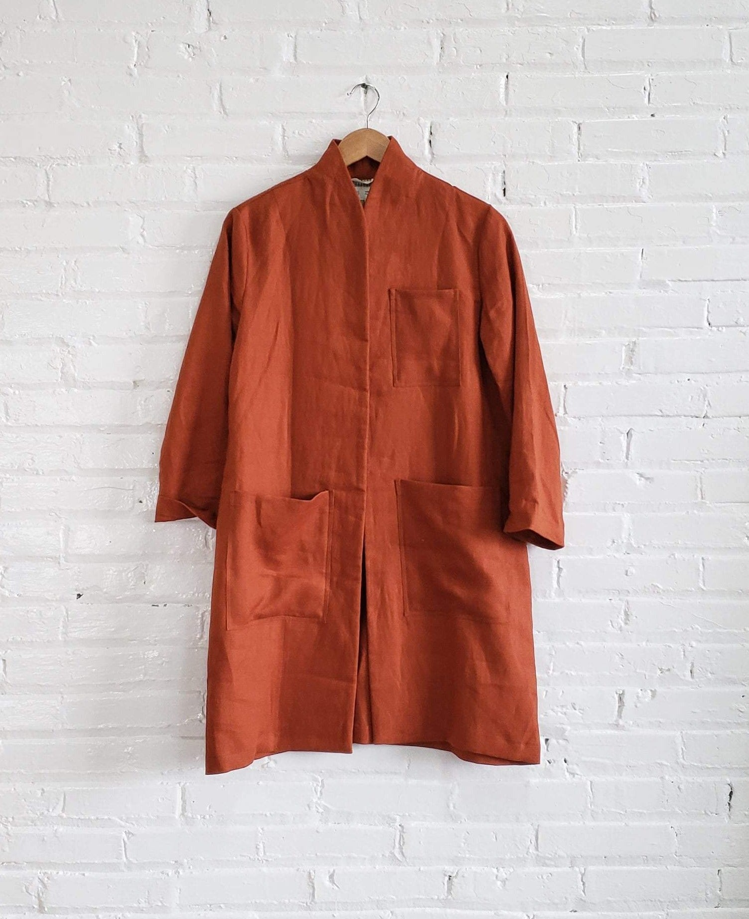 rust orange linen labcoat hanging on white brick wall