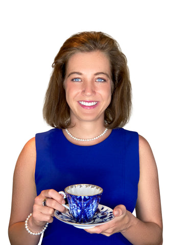 This is a photo of Mackenzie Bailey, founder of Steeped Content, drinking tea from a teacup, smiling a broad, sincere smile.