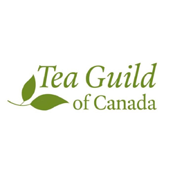 This is the logo for The Tea Guild of Canada, to which Mackenzie Bailey belongs. The name of the organization is written in green cursive, and a matching green tea leaf is located in the lower left.
