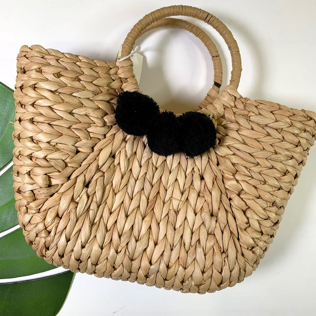 straw handbag with black pom pom