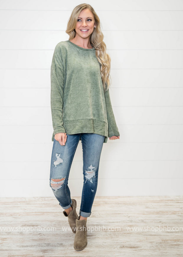 This Simple Things sweater in sage is all the rage, pairing it with denim and booties for a cozy yet stylish look.