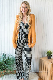 Our striped tank jumpsuit in black is perfect layered with a mustard cardigan