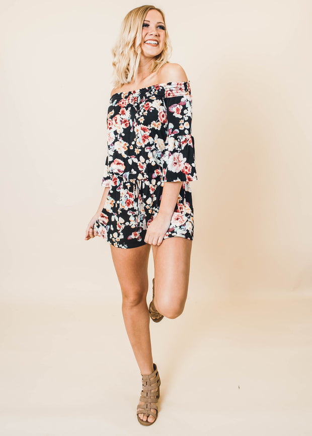 Black floral off the shoulder short romper featuring a cinched waist