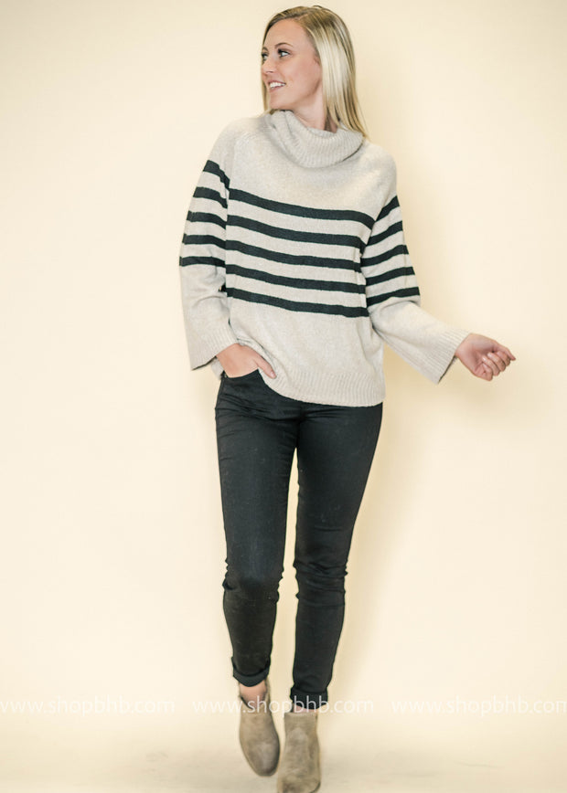 Long shot of our Turtleneck sweater in beige paired up black denim