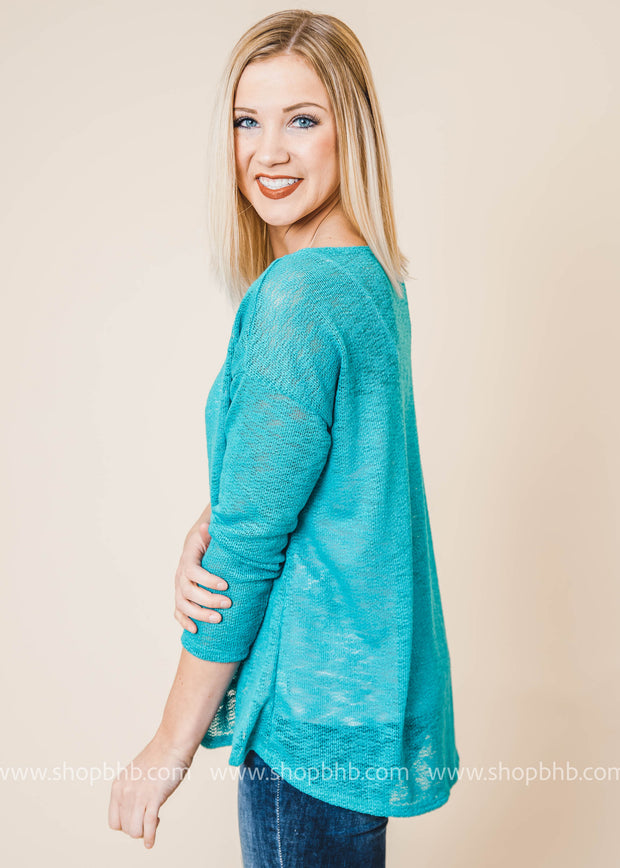 Knit sweater features a scoop neckline, long sleeves with dropped shoulders, slight high-low hemline with short side slits, and ribbed cuffs and hem.