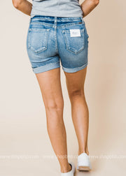 Light wash denim shorts feature a mid-rise waist, classic five pocket design, and distressing.